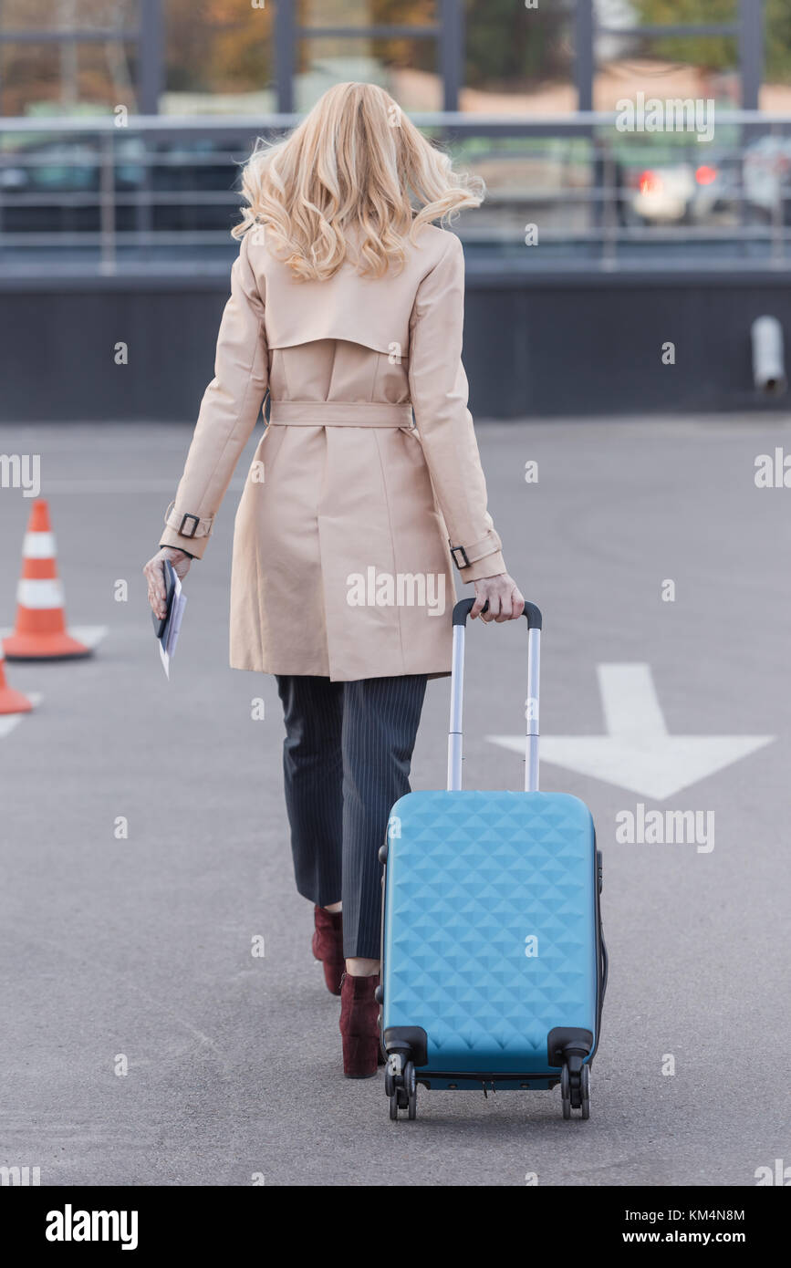 woman in trench coat walking with luggage - Stock Image