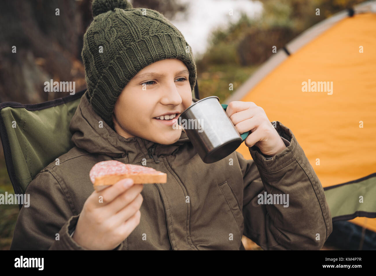 boy drinking tea and eating sandwich - Stock Image