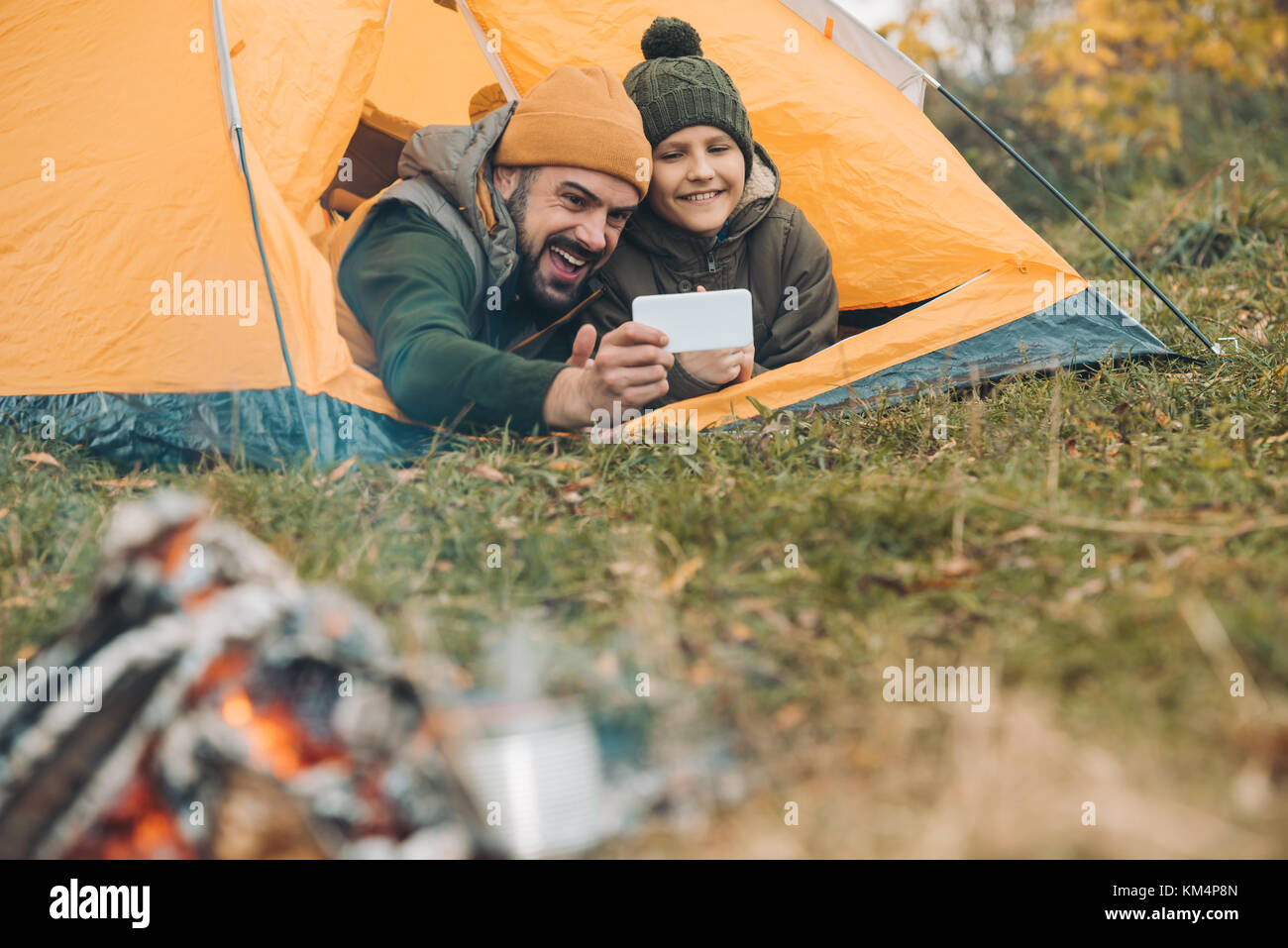 Father and son taking selfie with smartphone - Stock Image