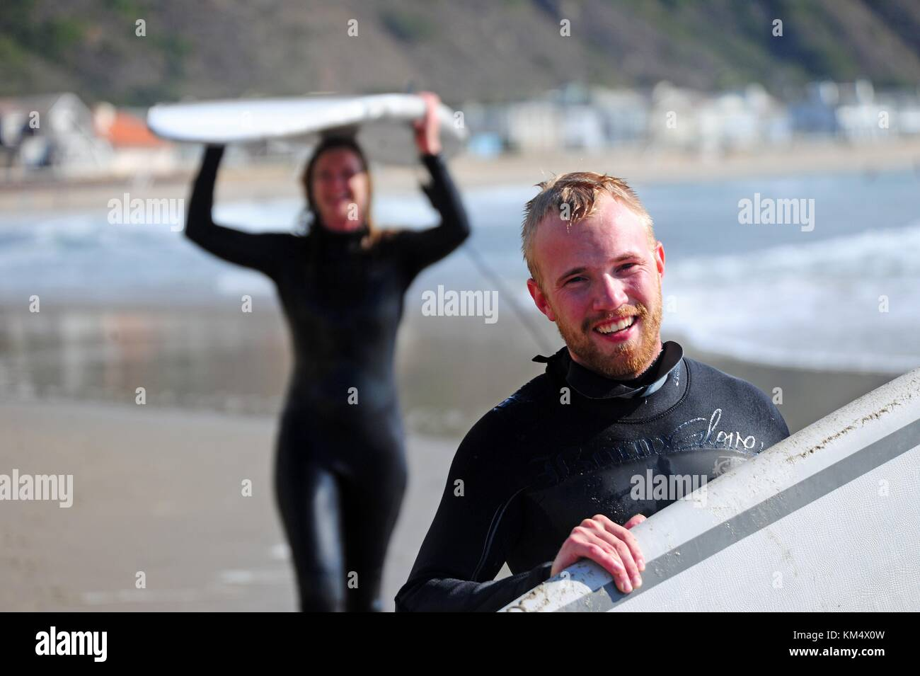 Military members from the Defense Language Institute Foreign Language Center try their hand at surfing along the - Stock Image