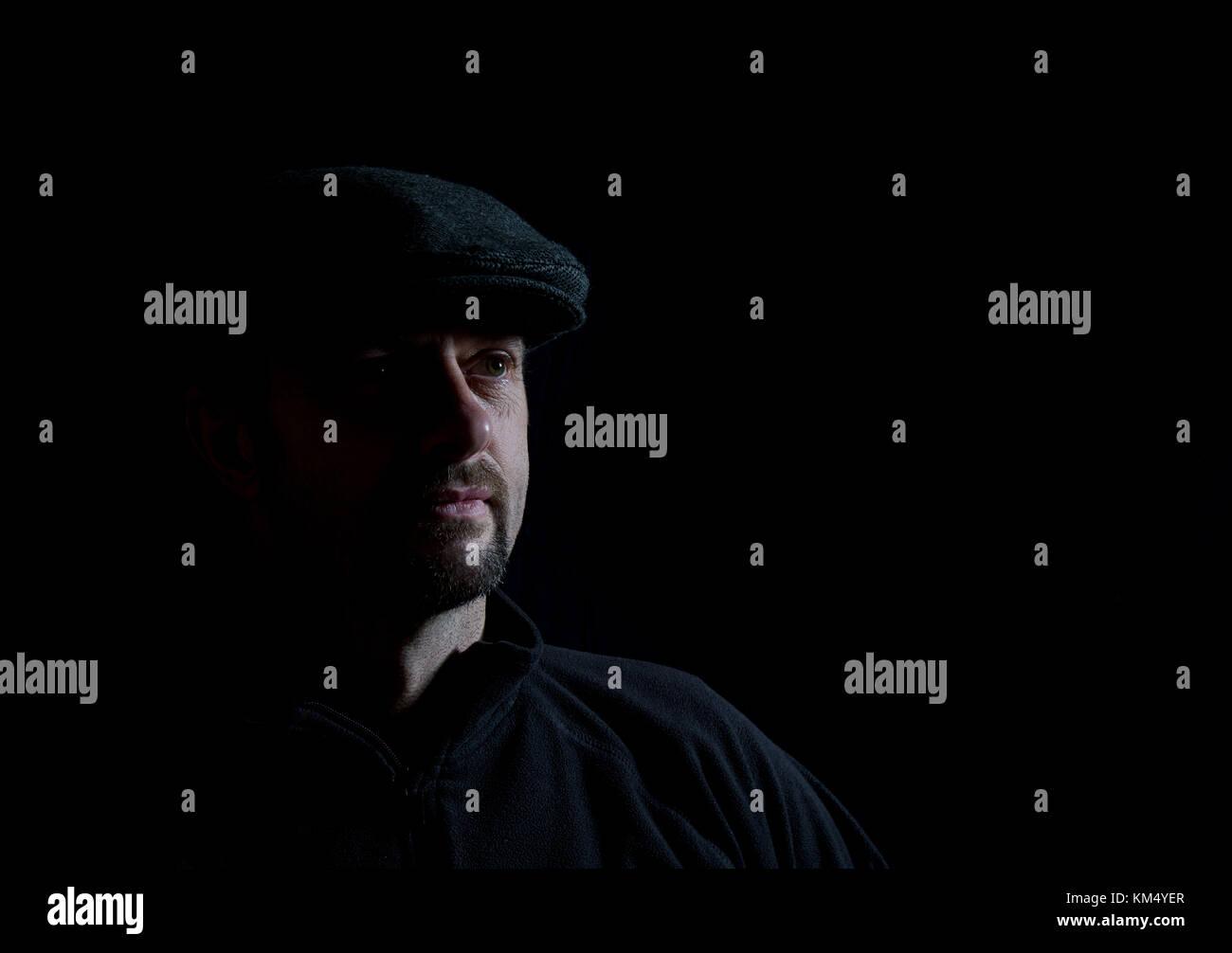 Low-key photo portrait of bearded man in dark cap, half-lit face, pensive pose. Low-key lighting, black background - Stock Image