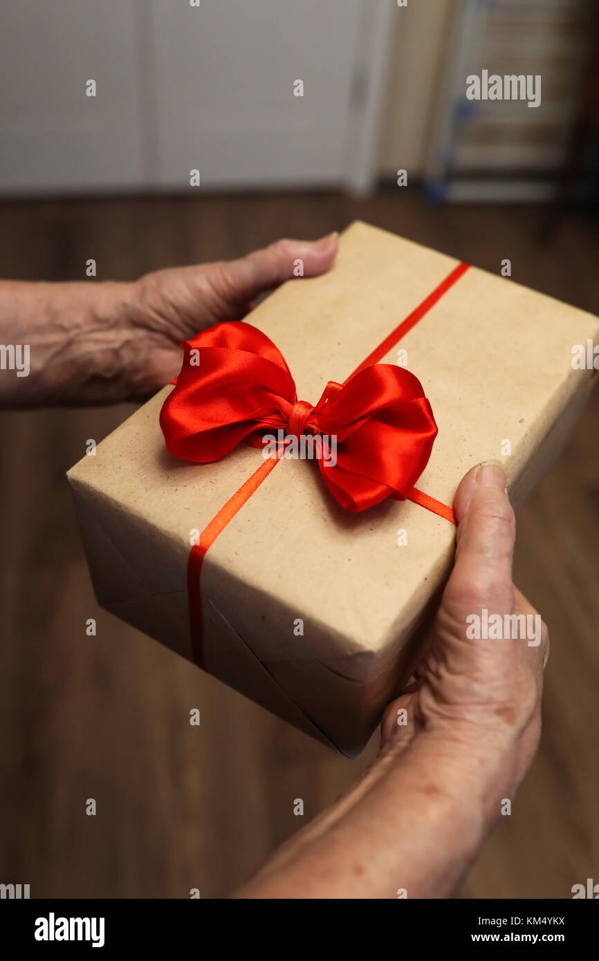 gift box with red bow in grandmother hands - Stock Image