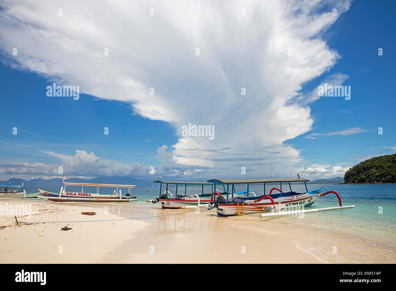 Outrigger tourist boats on idyllic tropical beach of the islet Gili Nanggu, part of the Gili Islands, island Lombok, - Stock Image