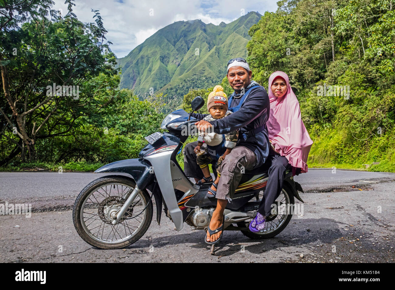 Indonesian family with toddler riding motorcycle through tropical rain forest on the slopes of Mount Rinjani, volcano Stock Photo