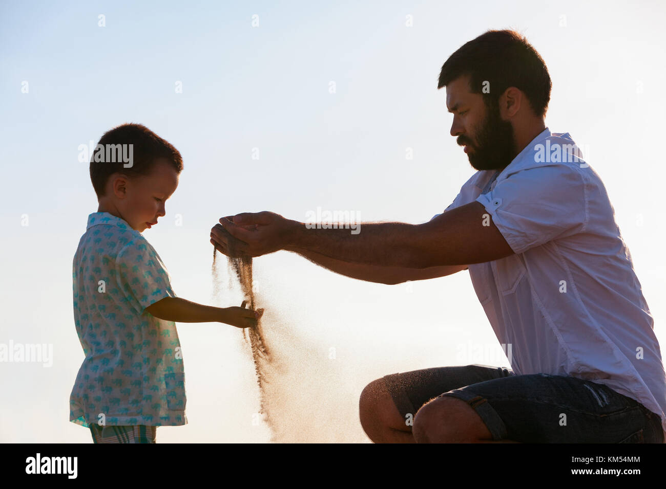 Happy family on sunset sea beach. Father, baby son play with sand slipping through man hand fingers. Child catching - Stock Image