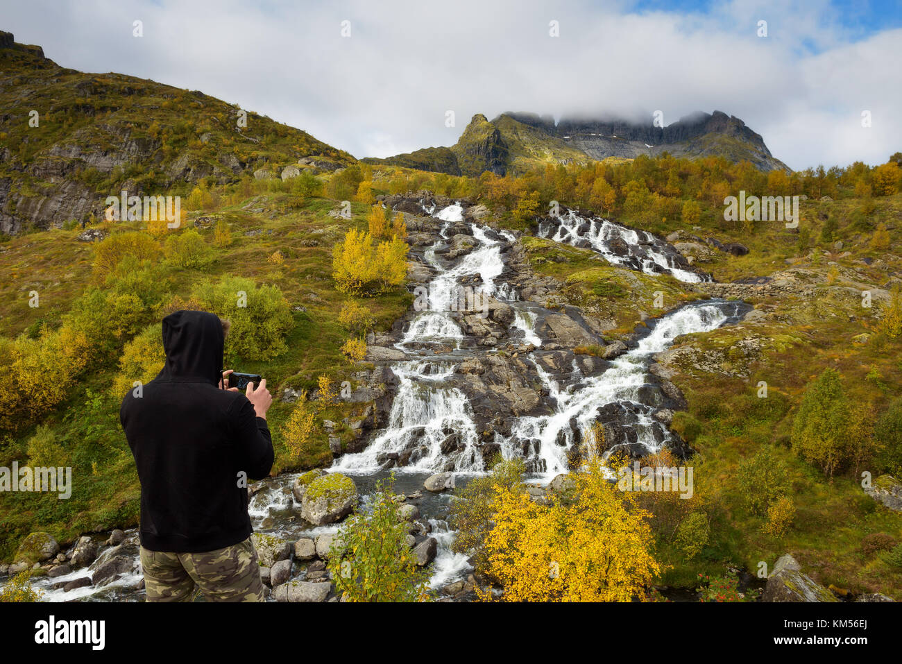 Tourist photographing Lofoten waterfall with a mobile phone in Norway Stock Photo