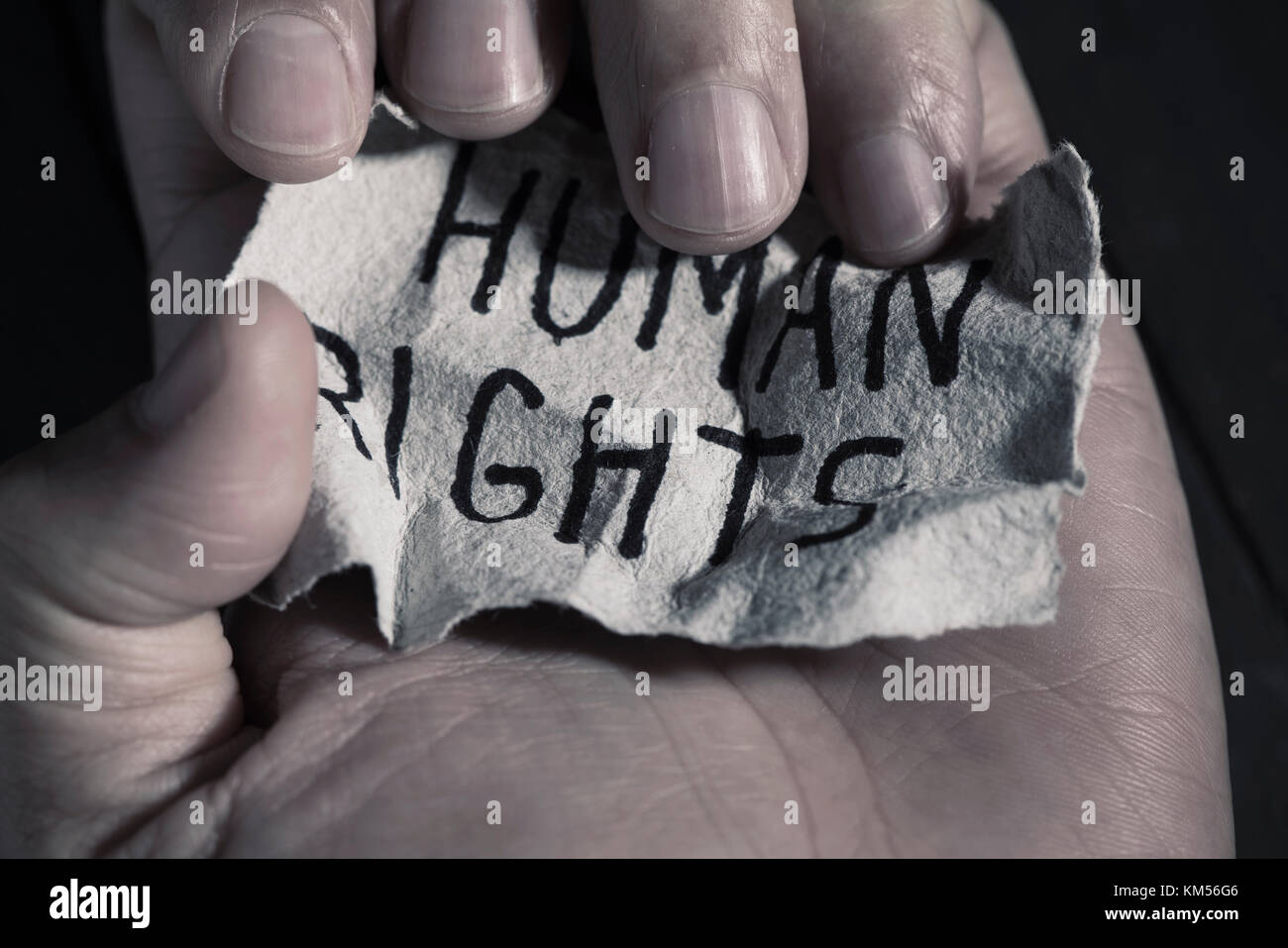 closeup of the hand of a young man with a piece of paper with the text human rights written in it - Stock Image