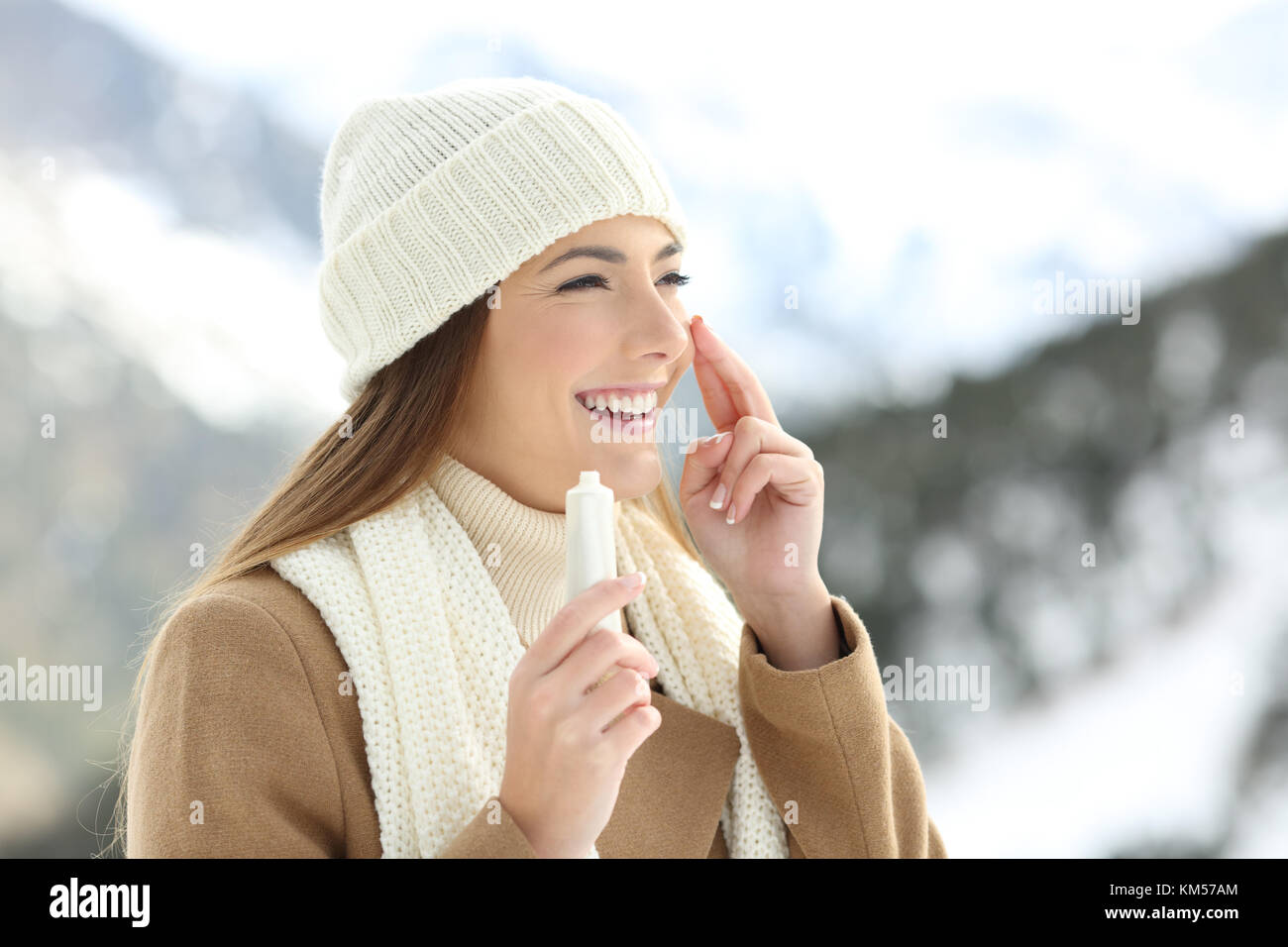 Lady hydrating her face skin with moisturizer cream in a snowy mountain in winter - Stock Image