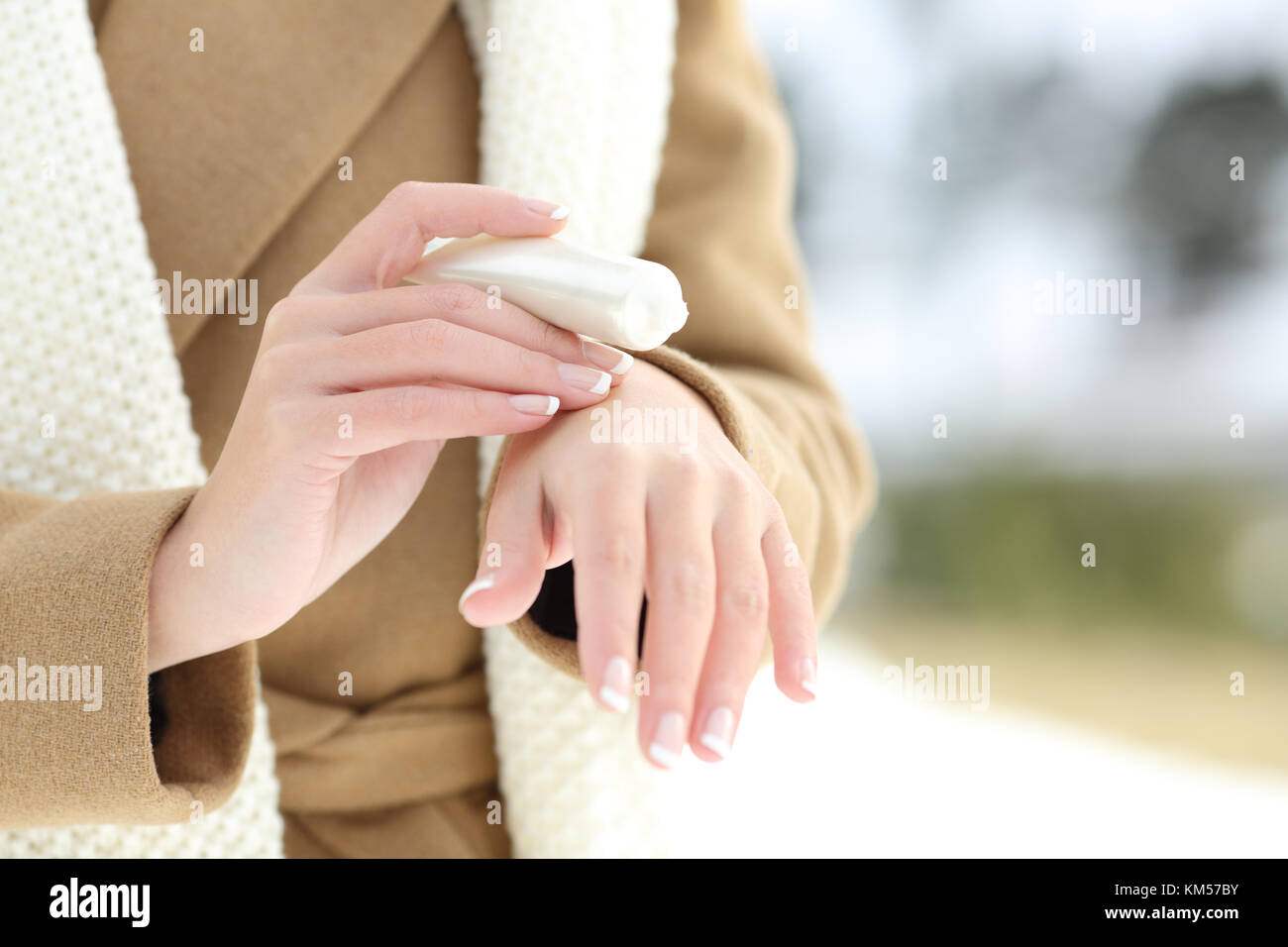 Close up of a woman hydrating hands with moisturizer cream in winter with a snowy mountain in the background - Stock Image
