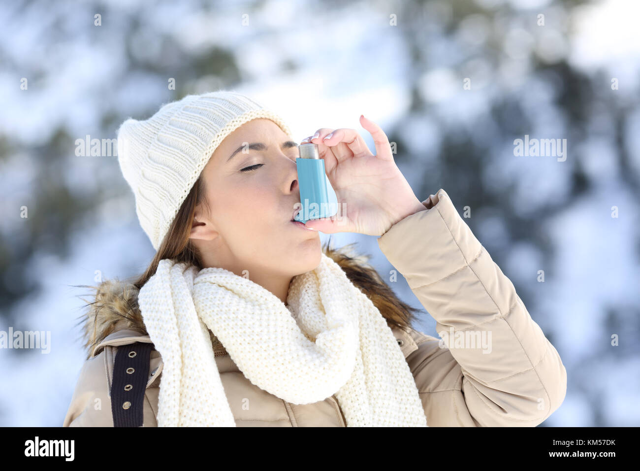 Portrait of a woman using an asthma inhaler in a cold winter with a snowy mountain in the background - Stock Image