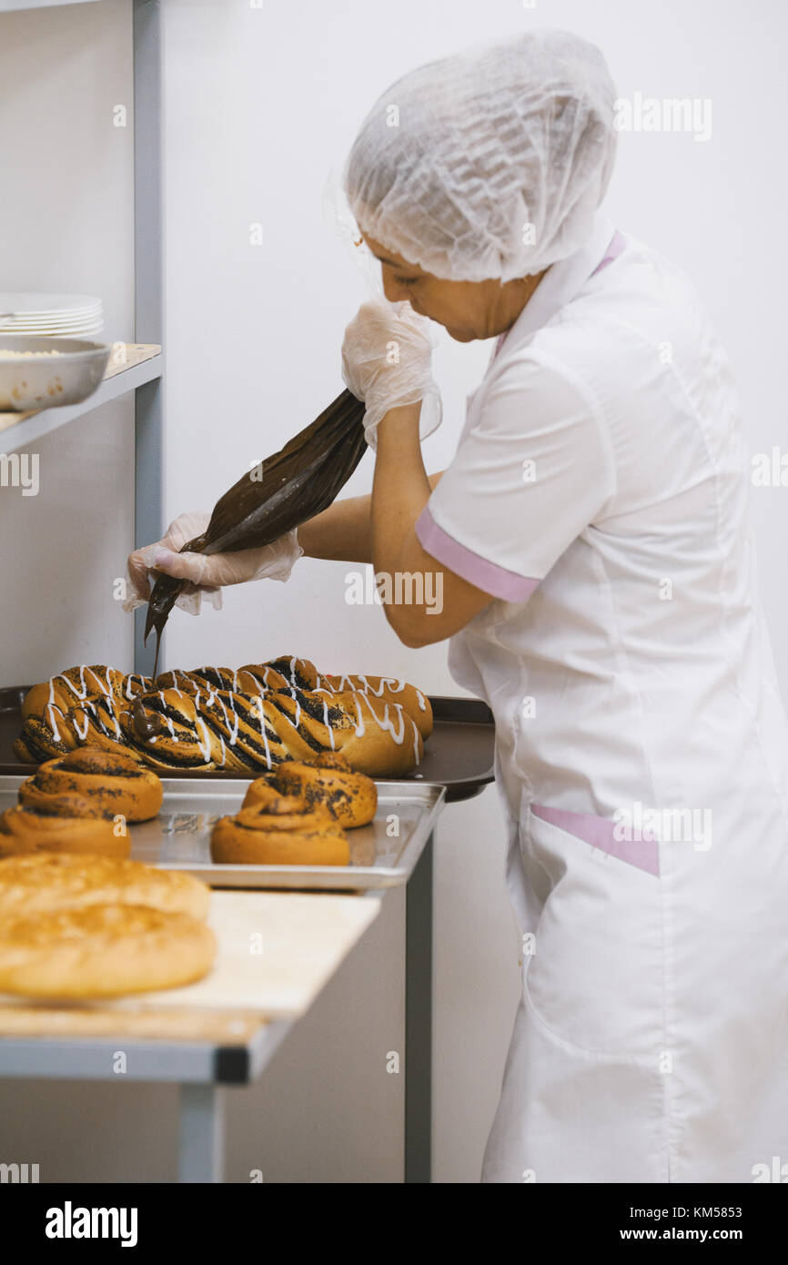 Adult woman in uniform bakes cakes in the bakery - Stock Image