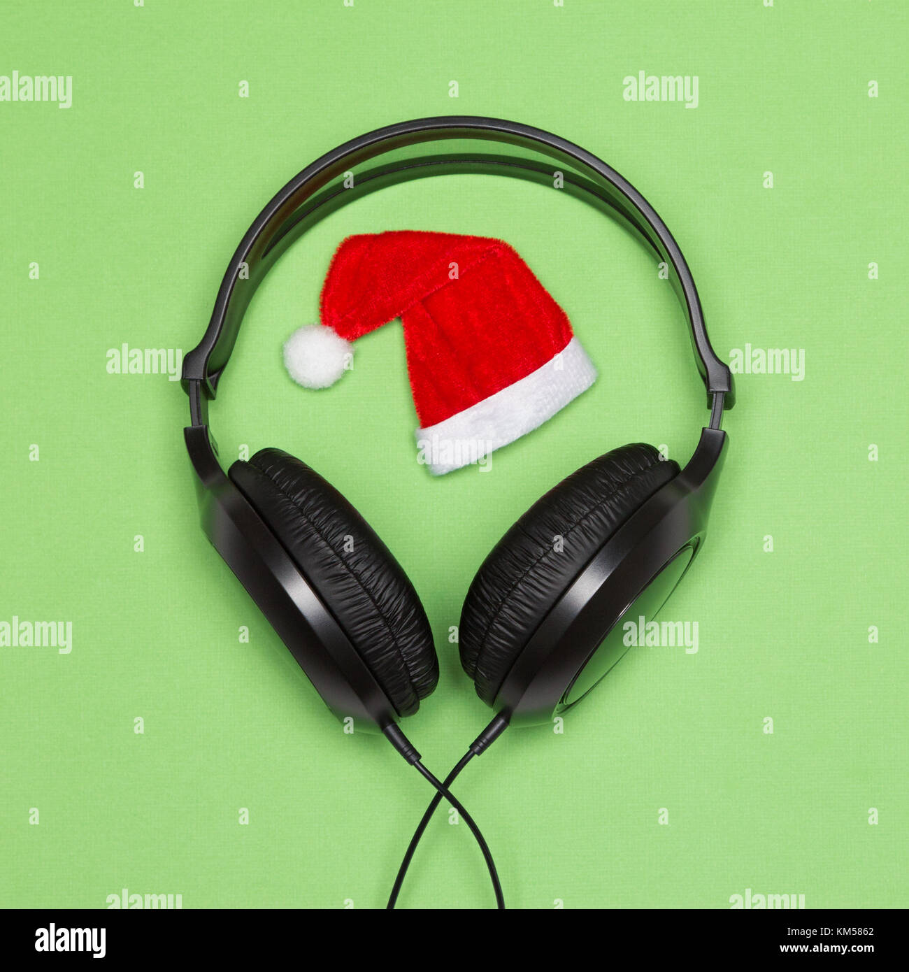 Headphones and Santa hat. Christmas songs minimal concept - Stock Image