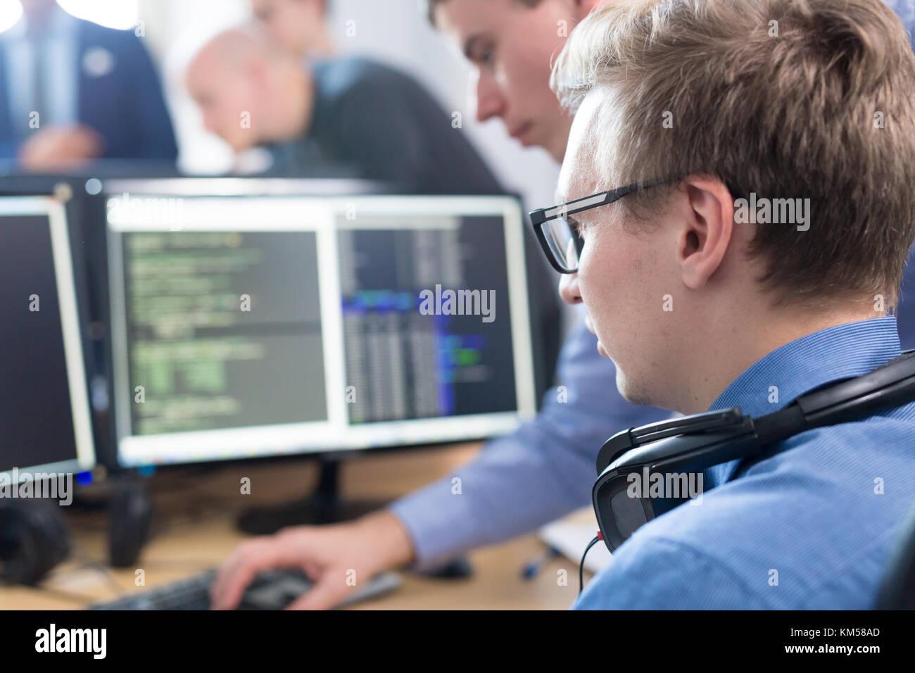 Startup business problem solving. Software developers working on desktop computer. - Stock Image