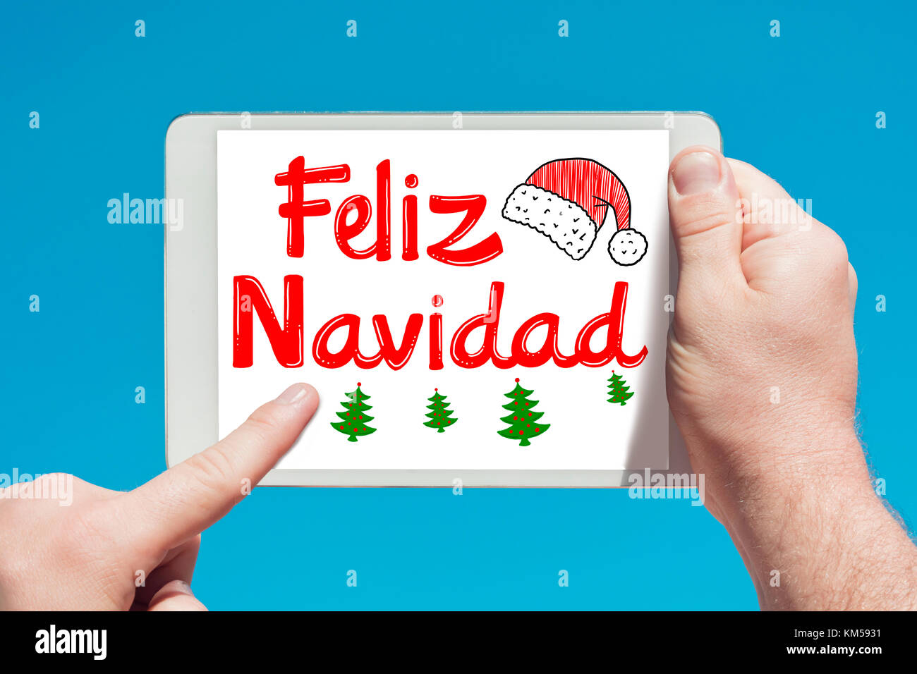 Man holding a tablet device with text in Spanish 'Feliz Navidad (Merry Christmas) and touching the screen with - Stock Image