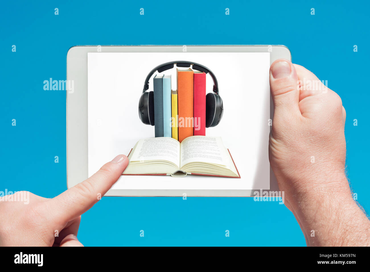 Man holding a tablet device showing audiobooks concept and touching the screen with a finger with blue sky in background. - Stock Image