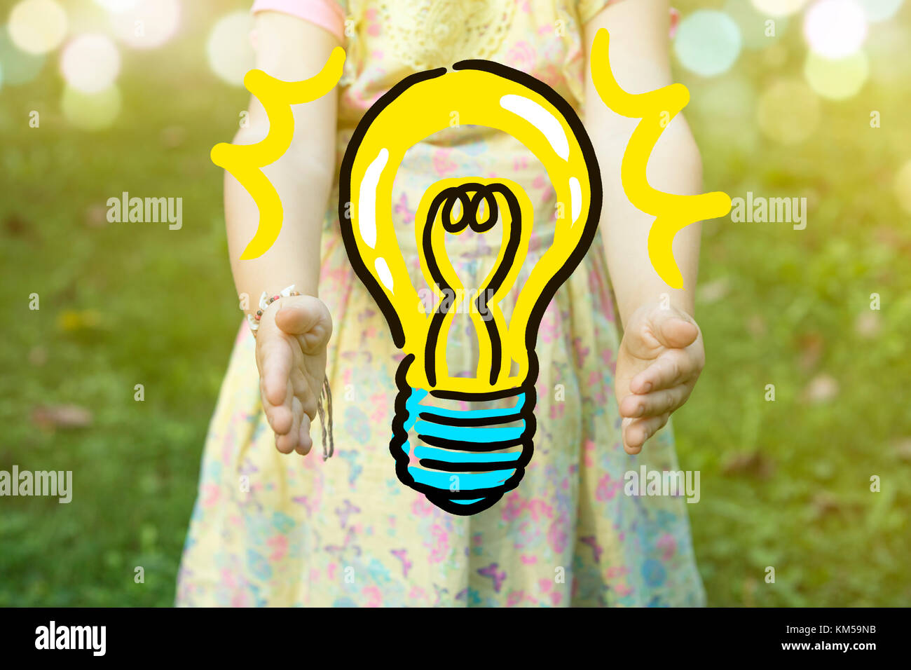 Child holding a light bulb drawing as idea concept, outdoors on a sunny day. Stock Photo