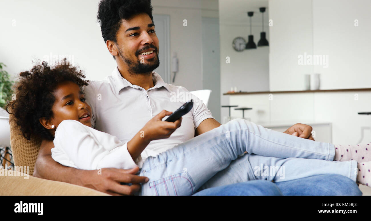 happy father and daughter and watching tv at home - Stock Image