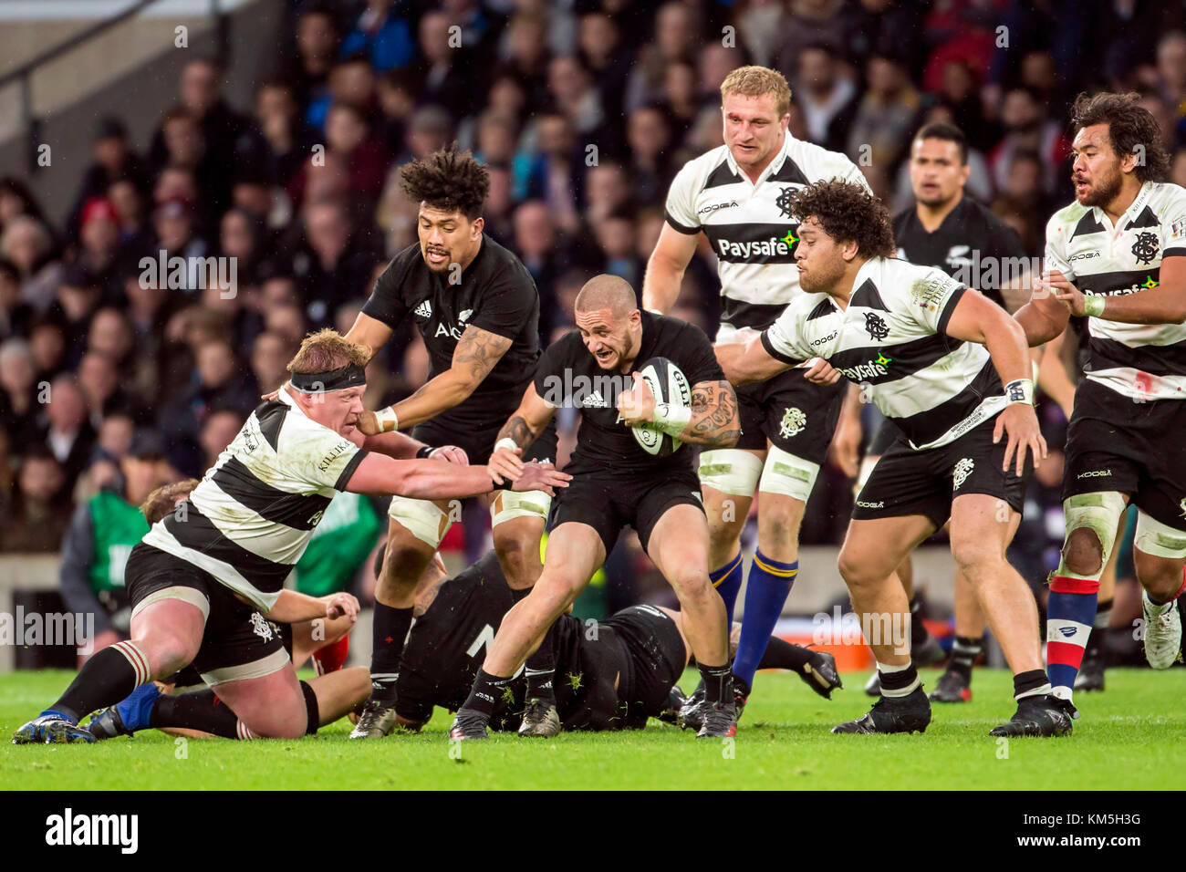 New Zealand's TJ Perenara (All Blacks, 9) attempting to defend the ball against Jacques van Rooyen (Barbarians, - Stock Image