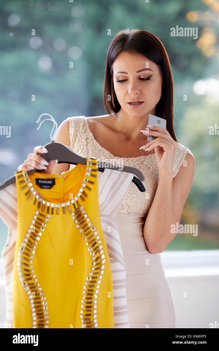 Girl looking doubtful purchasing clothes - Stock Image