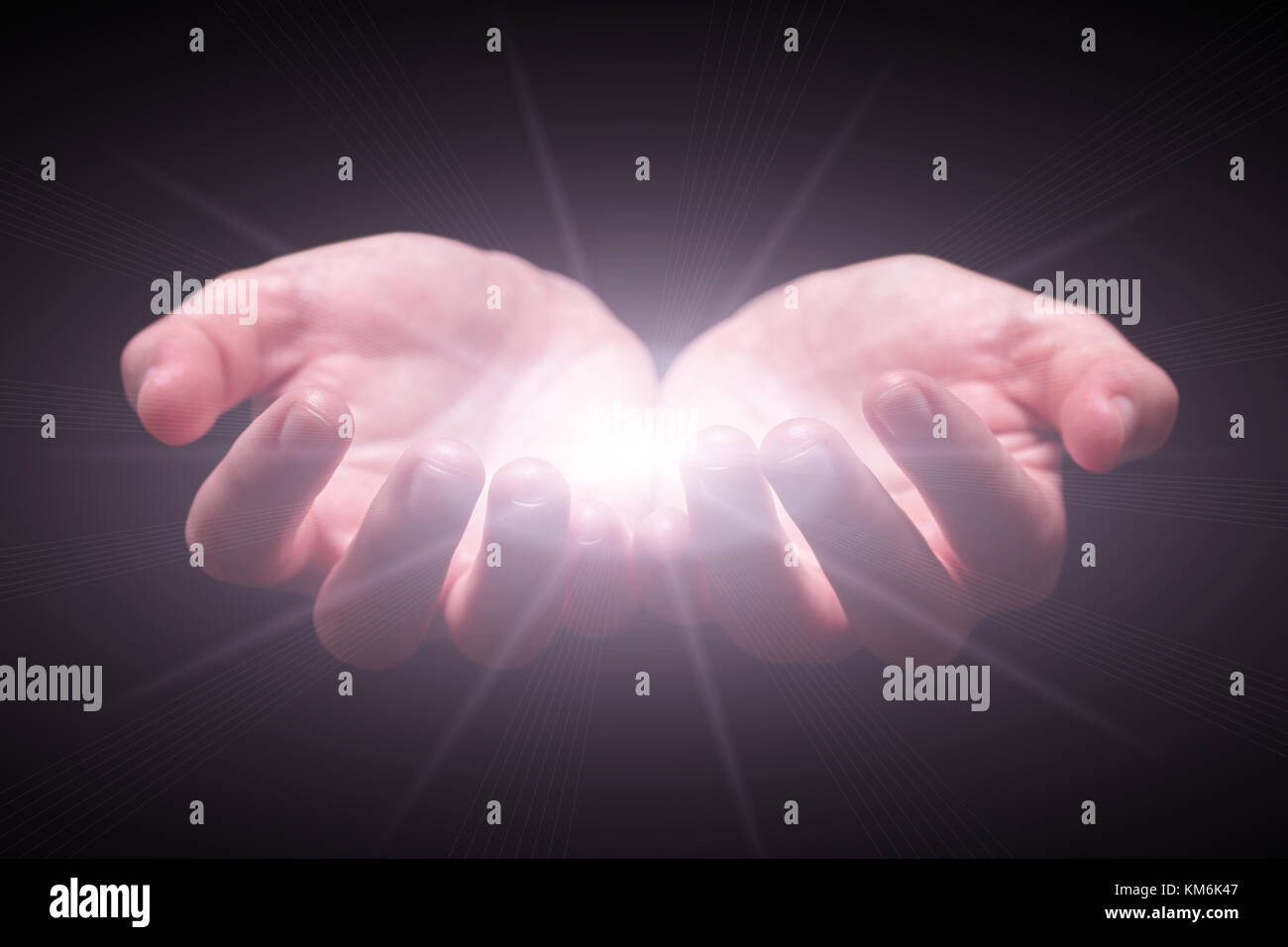 Woman hands cupped protecting and holding bright glowing radiant shining light. Emitting rays or beams expanding. - Stock Image