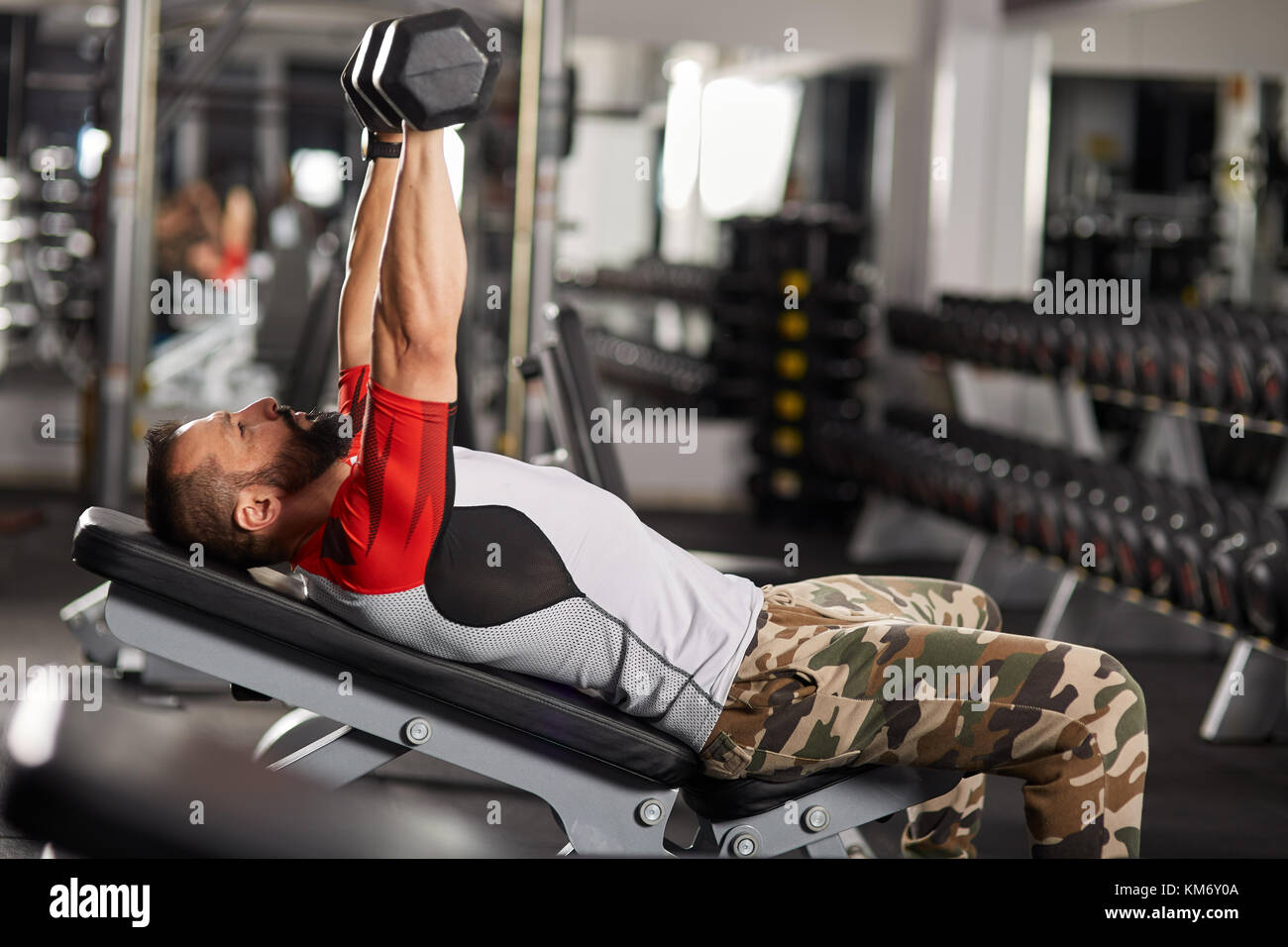 Man doing chest workout at inclined bench with dumbbells