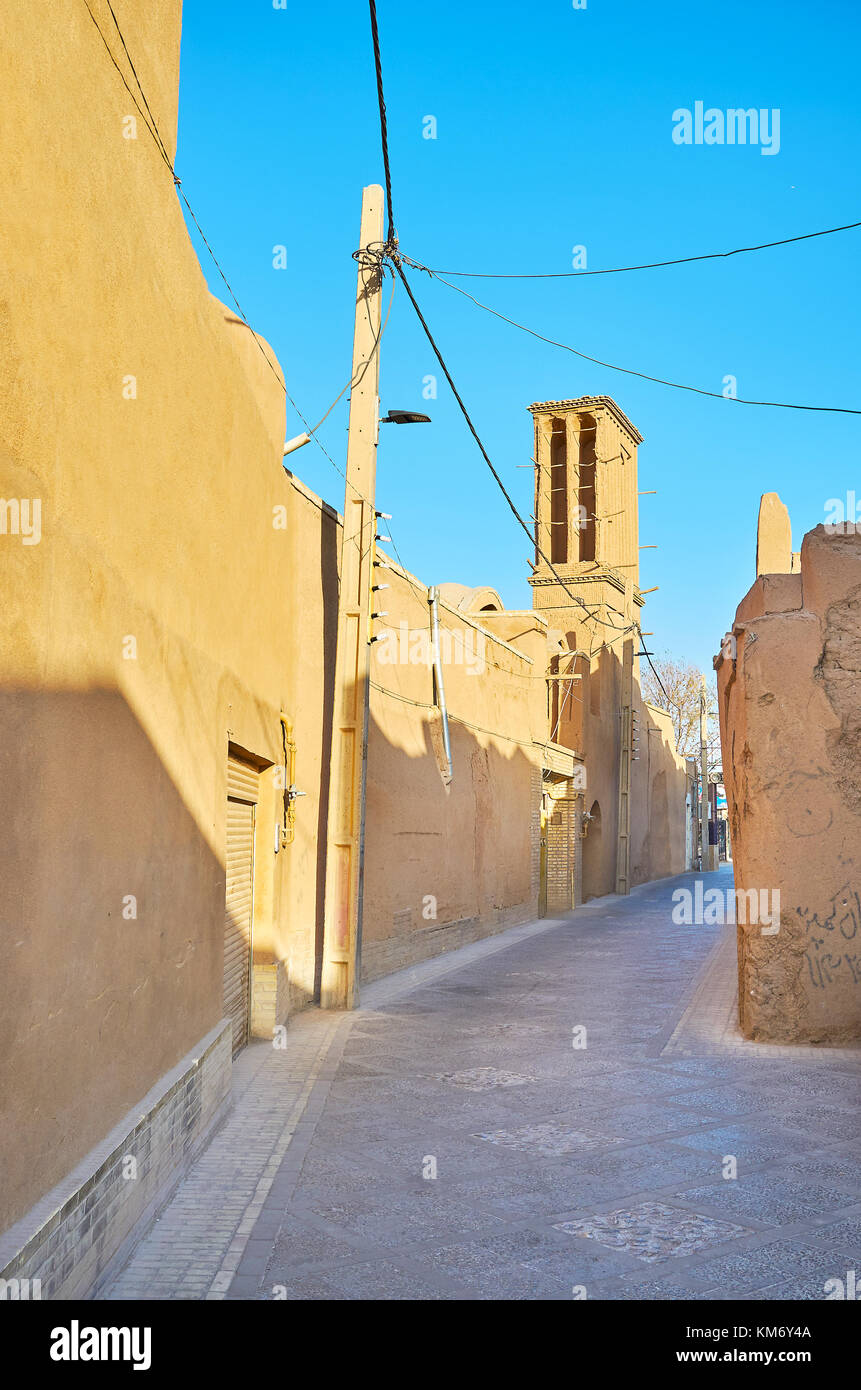 Narrow winding street of old town of Yazd with mud-brick badgir (windtower) on the background, Iran - Stock Image