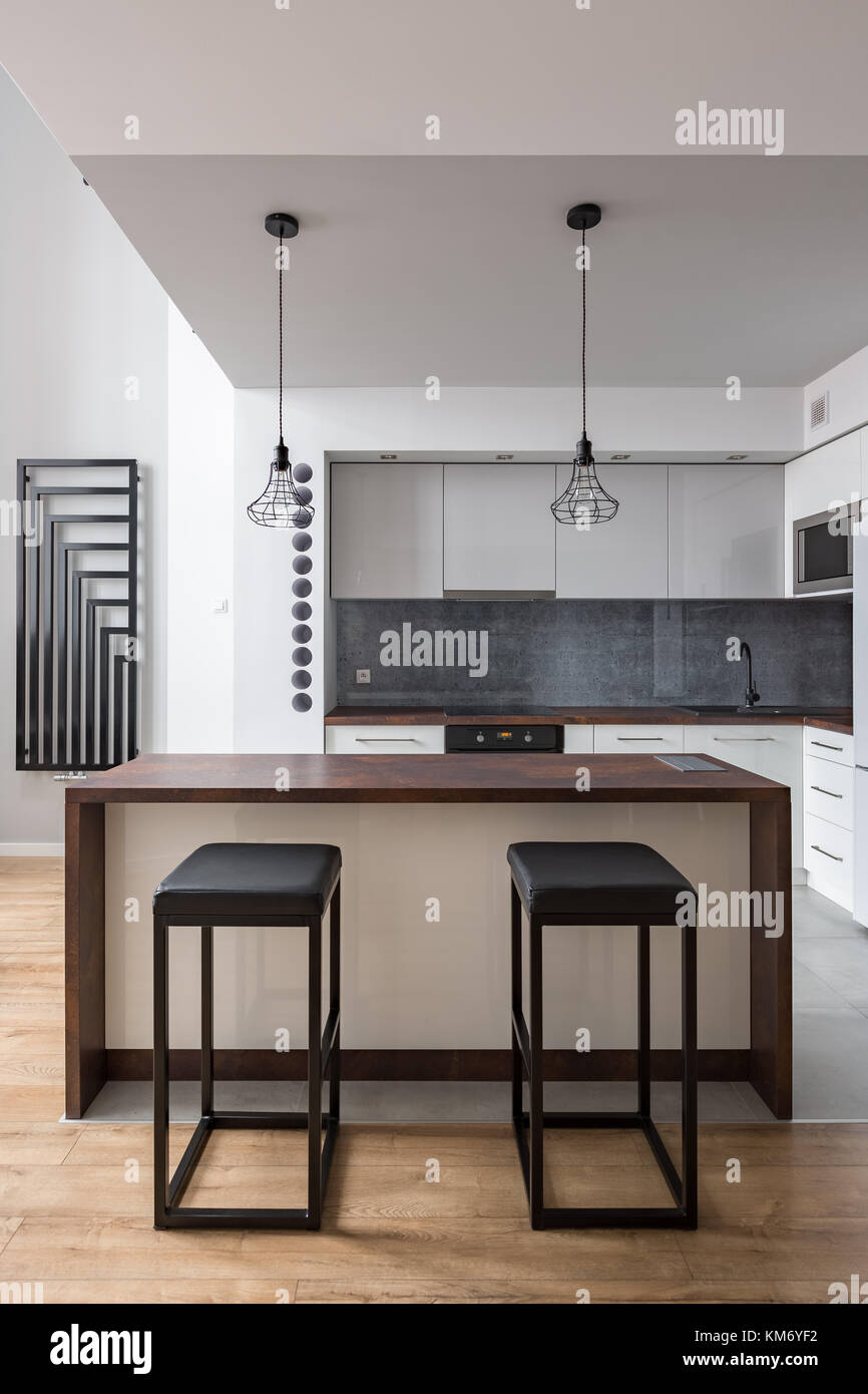 Modern Kitchen With Table Stools And Decorative Wall Radiator Stock Photo Alamy