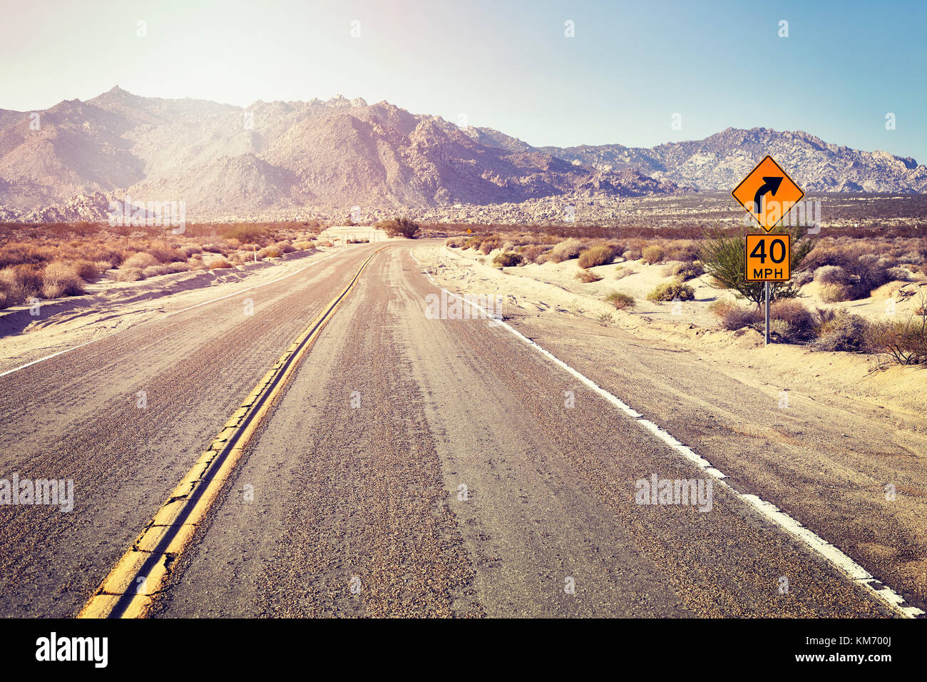 Desert highway with speed limit sign, color toned picture, travel concept, USA. Stock Photo