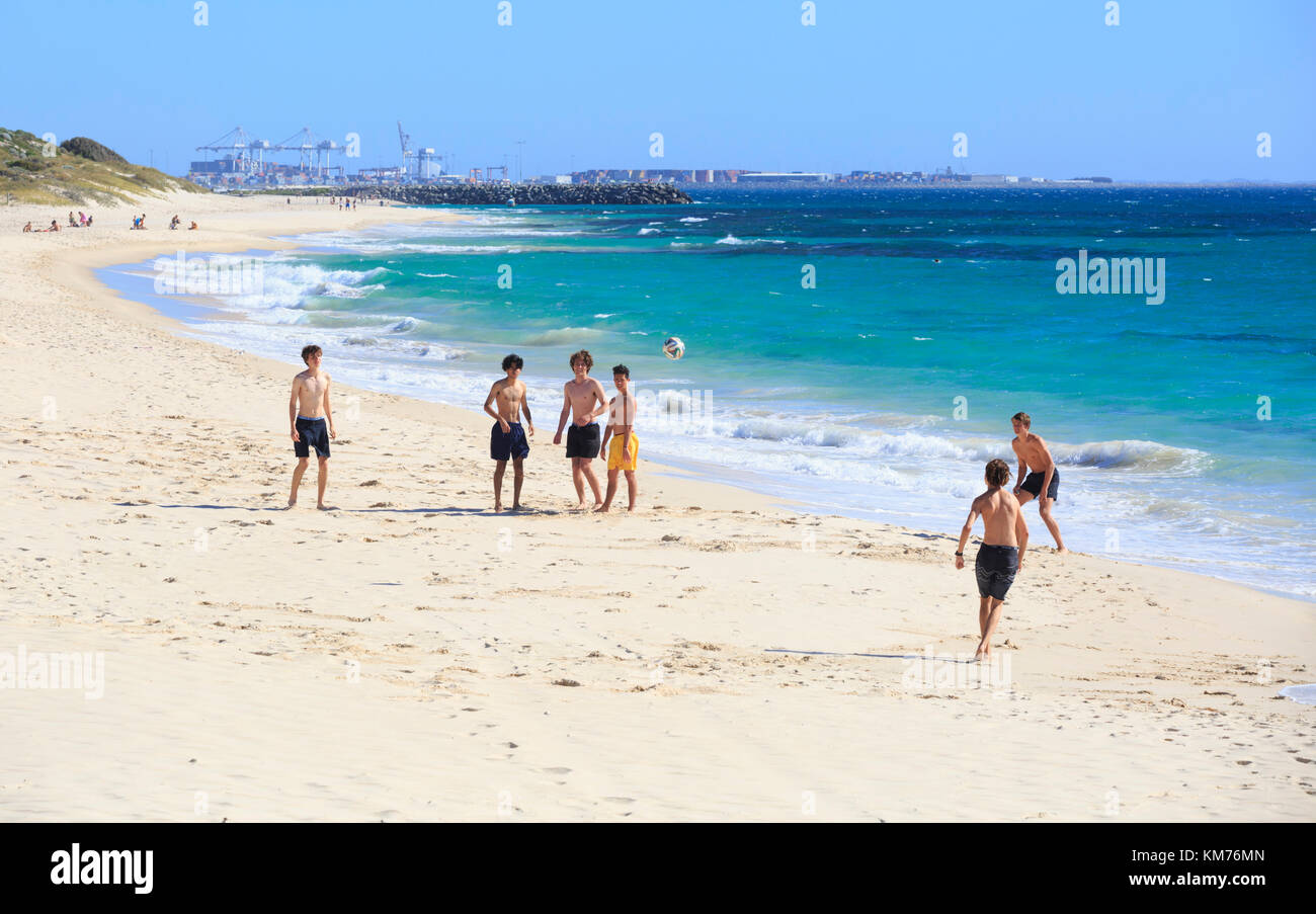 Teenage boys playing football on Cottesloe Beach in Perth, Western Australia - Stock Image