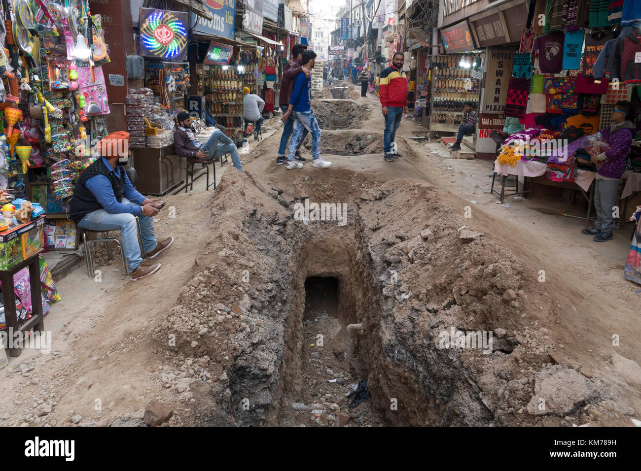 Shop keepers disrupted by drain laying in old town Amritsar, Pubjab, India - Stock Image