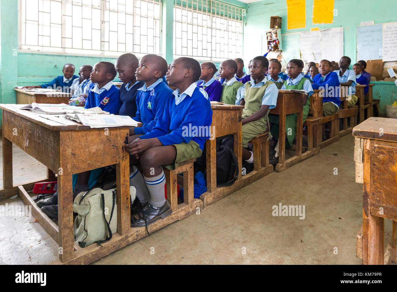 Secondary school children in uniform sat at desks listening to their teacher during class, Nairobi, Kenya - Stock Image