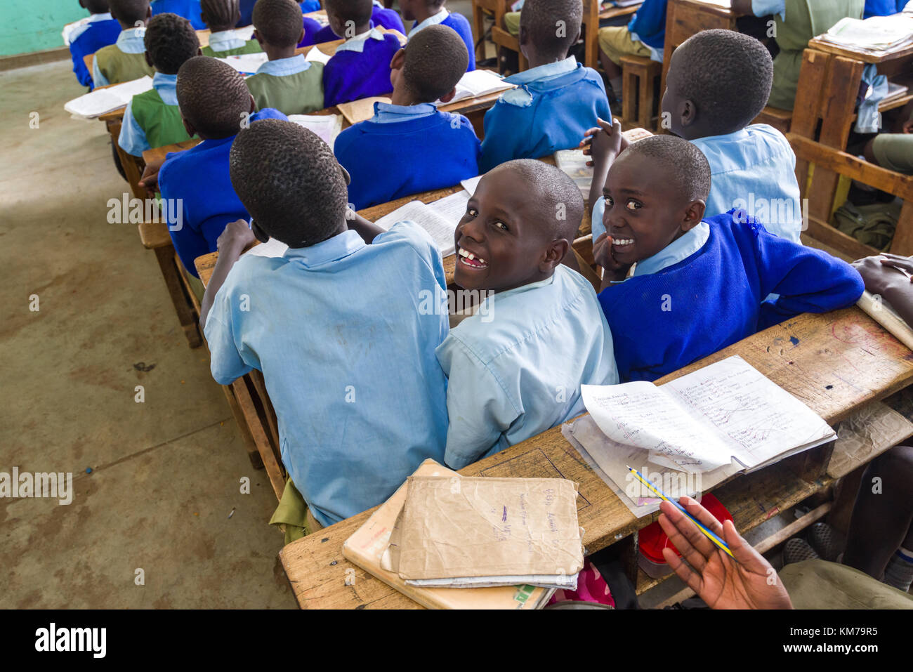 Secondary school children in uniform sat at desks smiling back at the camera during class, Nairobi, Kenya Stock Photo
