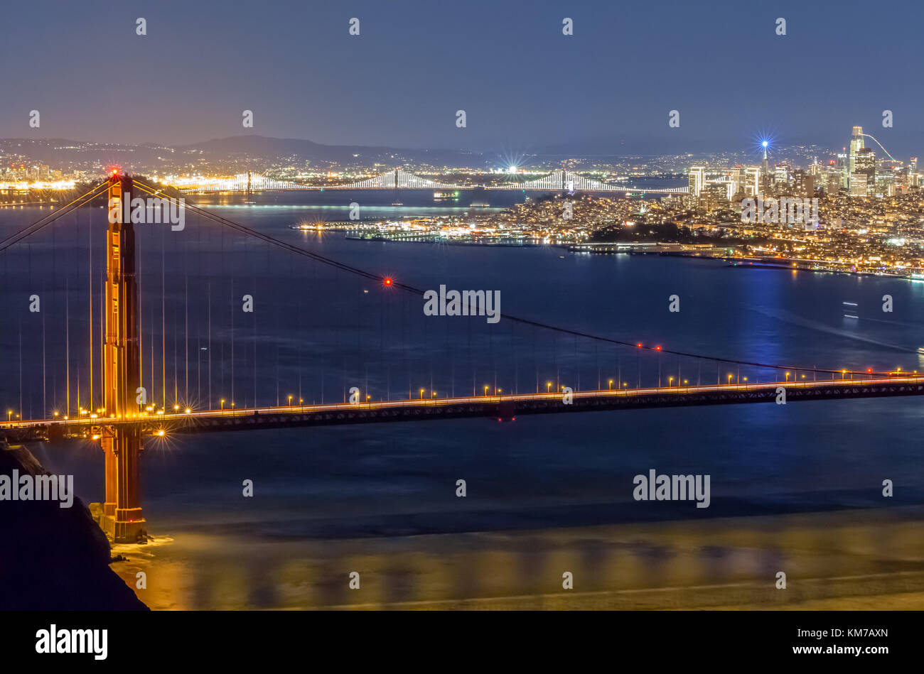Night time at the Golden Gate Bridge, with the  San Francisco City and East Bay cities in the back ground, California, - Stock Image