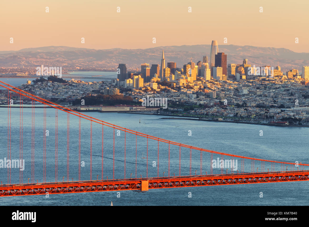 Evening sunlight lit up the San Francisco City high rises, with the Golden Gate Bridge on the foreground, California, - Stock Image