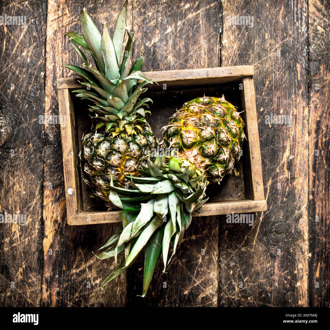 Fresh pineapple in an old box. On wooden background. - Stock Image
