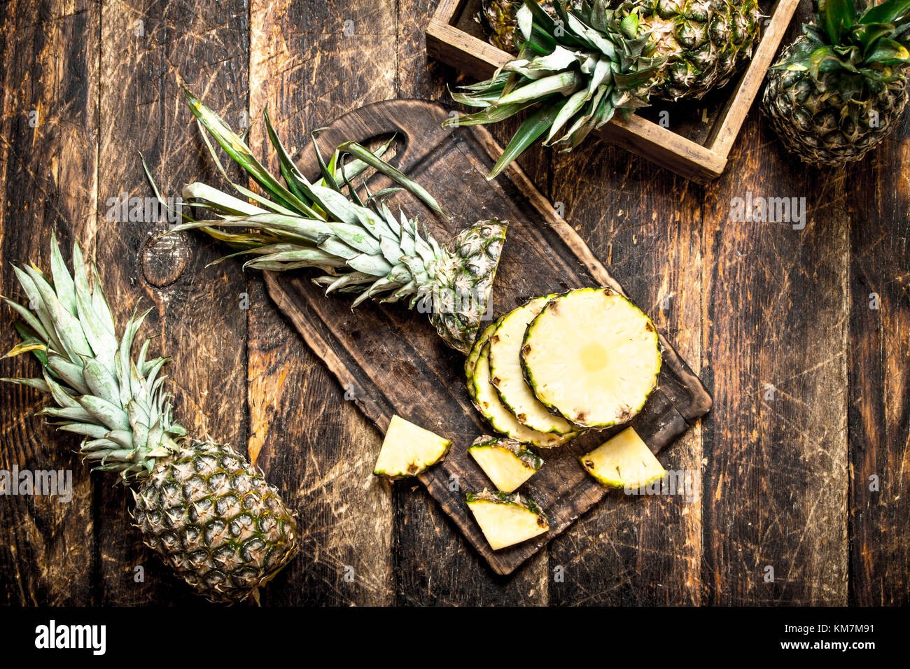 Sliced fresh pineapple. On the wooden background. - Stock Image