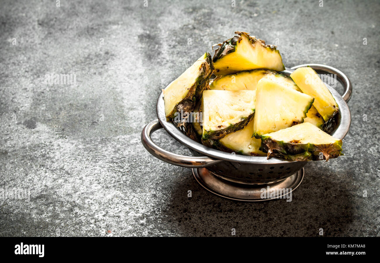 Pineapple in a bowl. On rustic background. - Stock Image