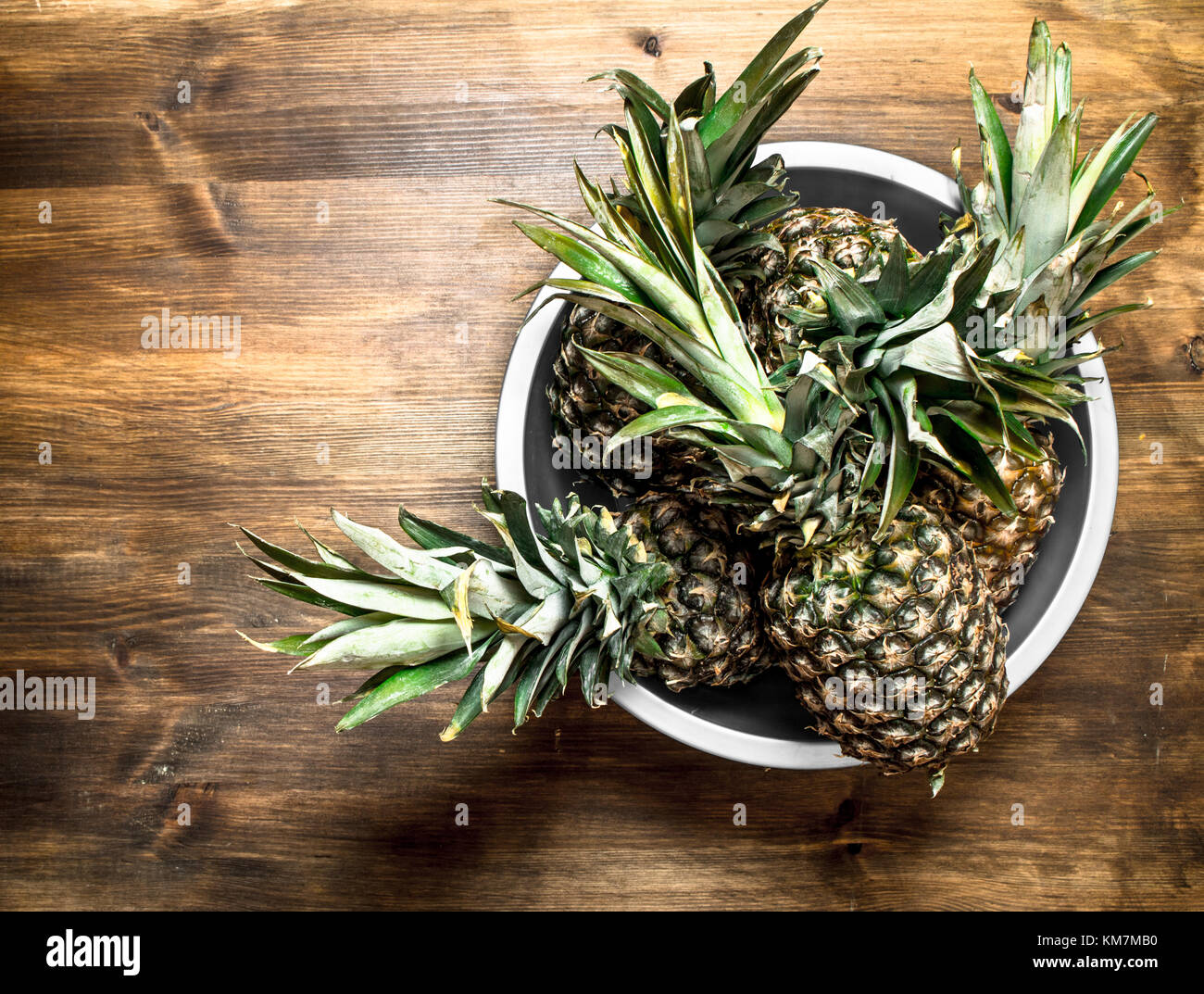 Ripe pineapple in a large bowl. On a wooden table. Stock Photo
