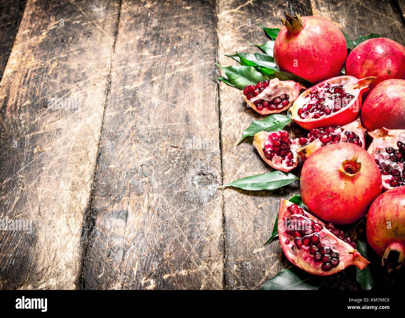 Ripe fresh pomegranates. On the wooden background. - Stock Image