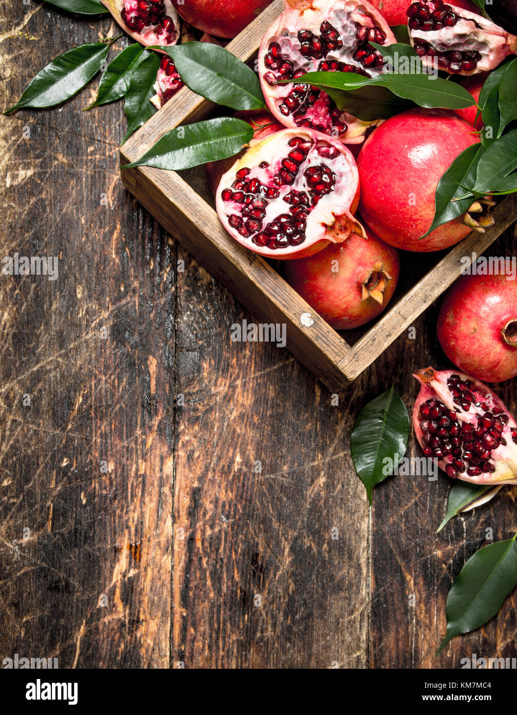 Fresh pomegranates in an old box. On wooden background. - Stock Image