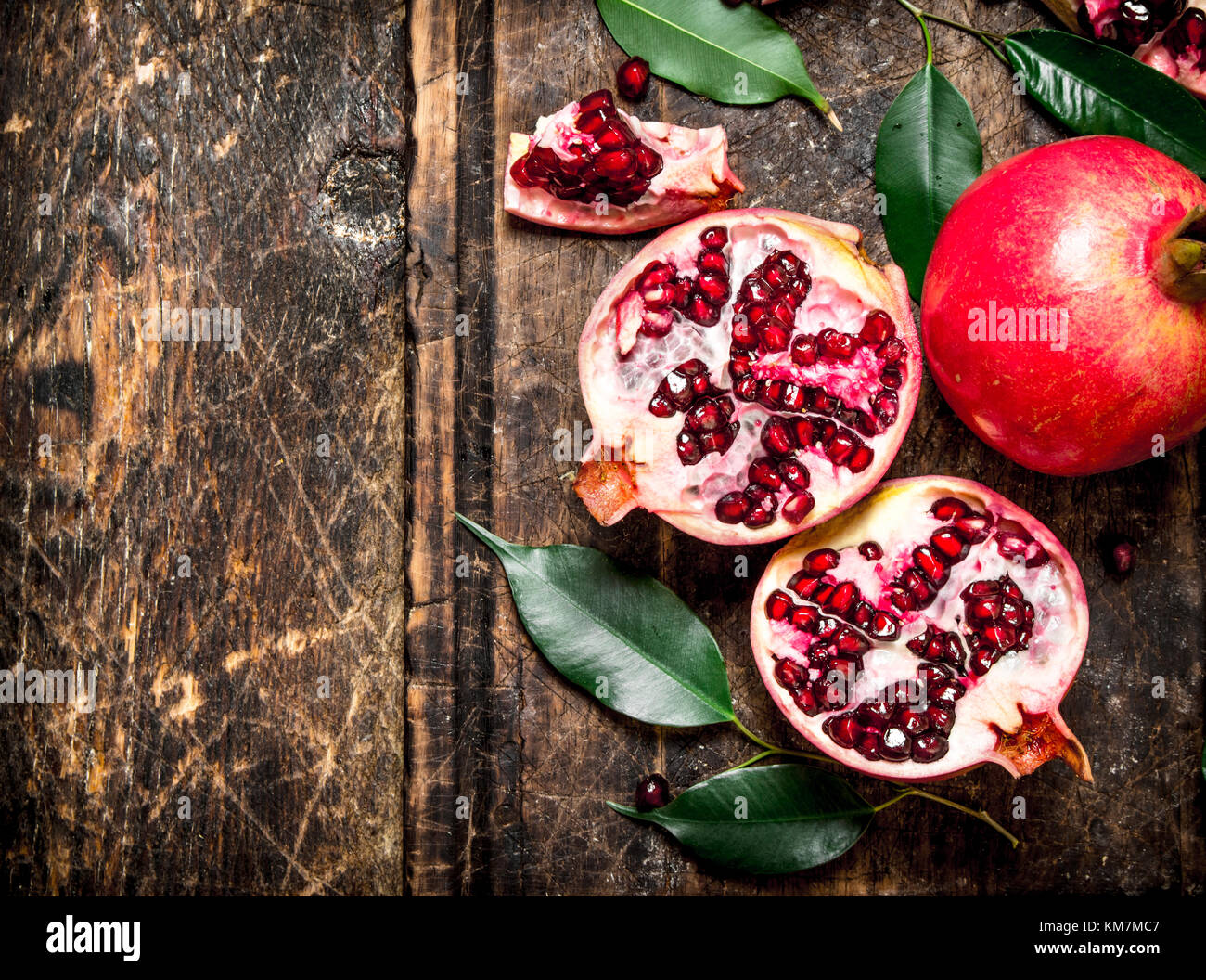Ripe fresh pomegranates. On the wooden background. - Stock Image