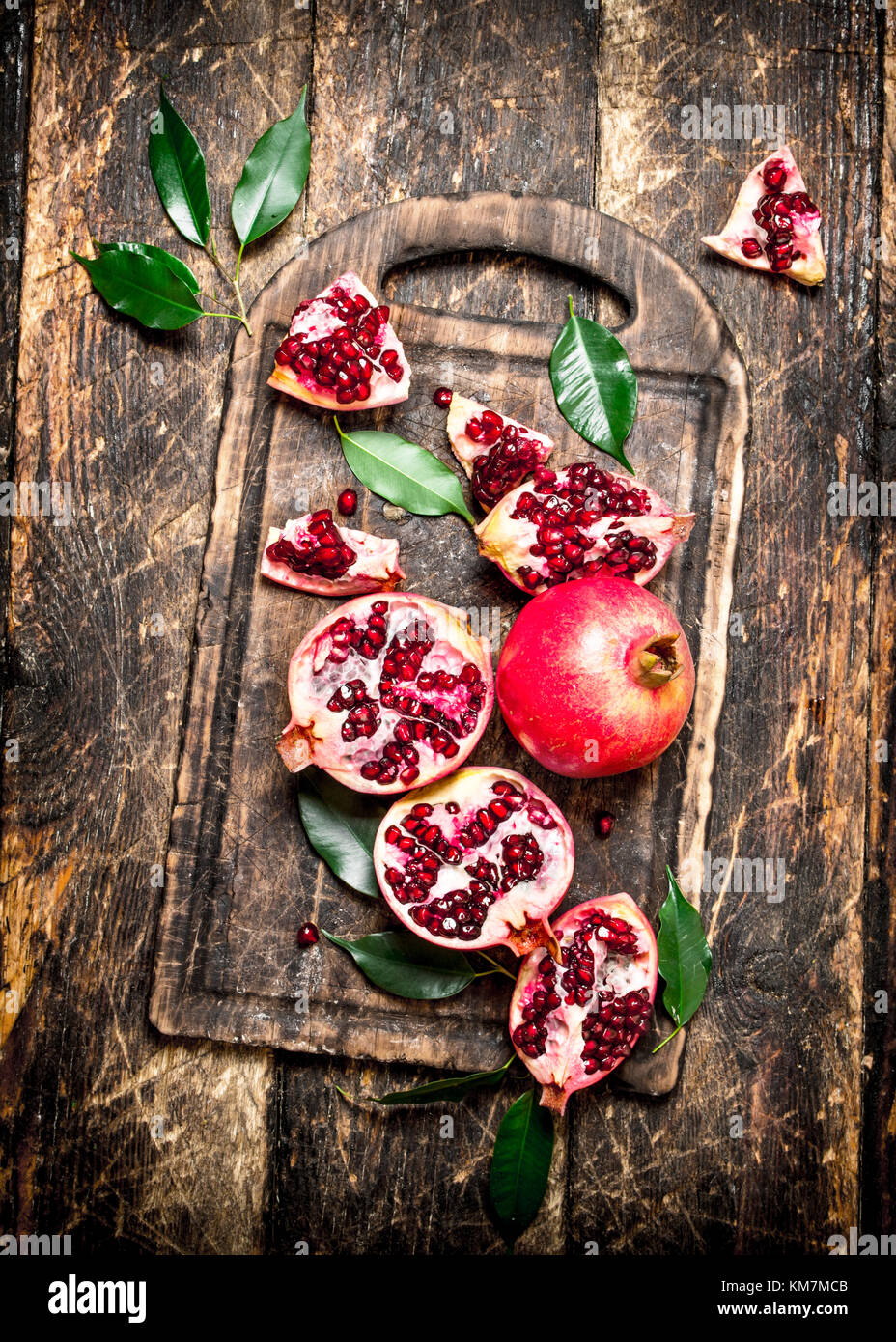 Ripe pomegranates on a cutting Board. On wooden background. - Stock Image