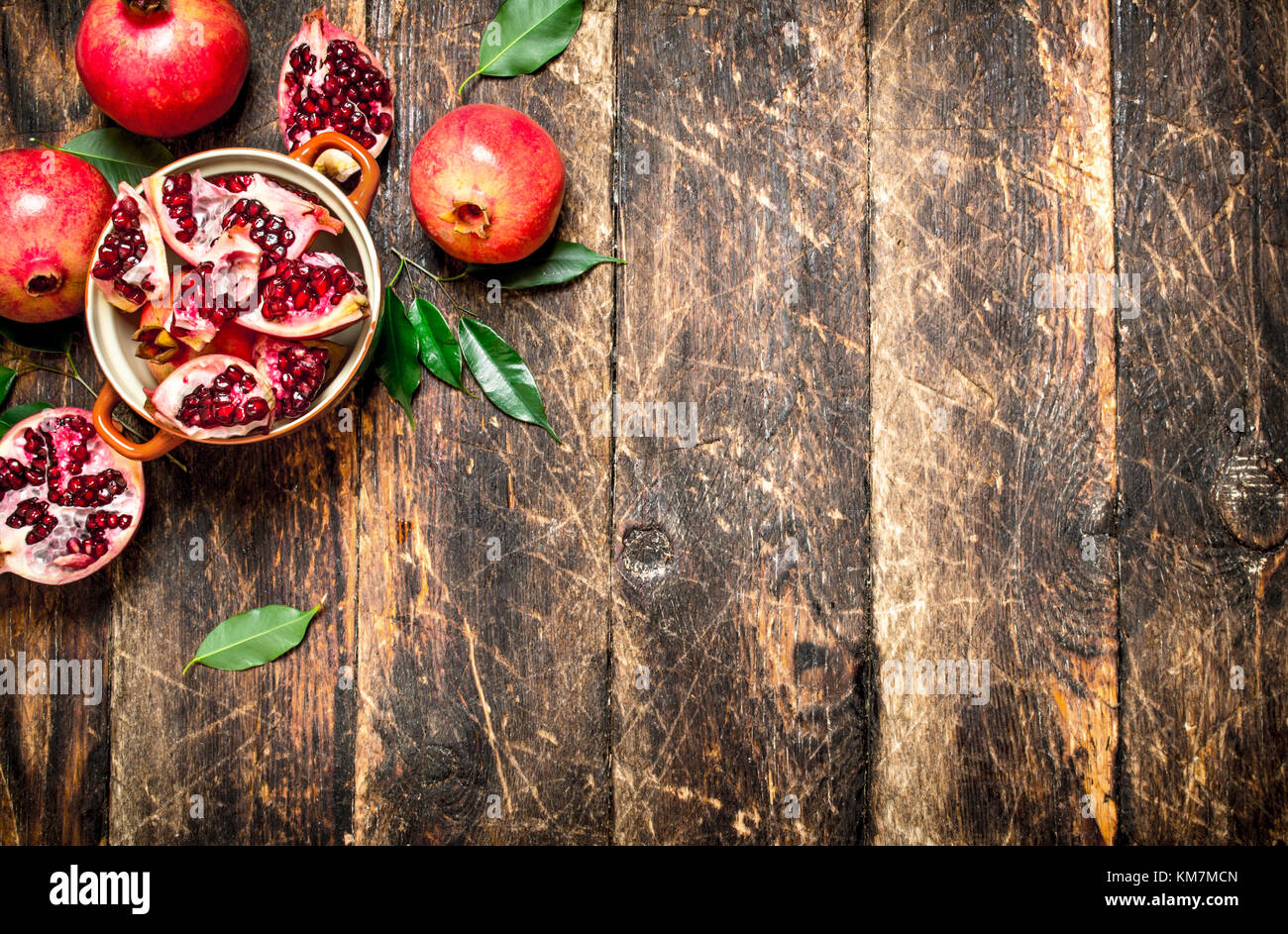 Fresh pomegranates in a bowl. On wooden background. - Stock Image