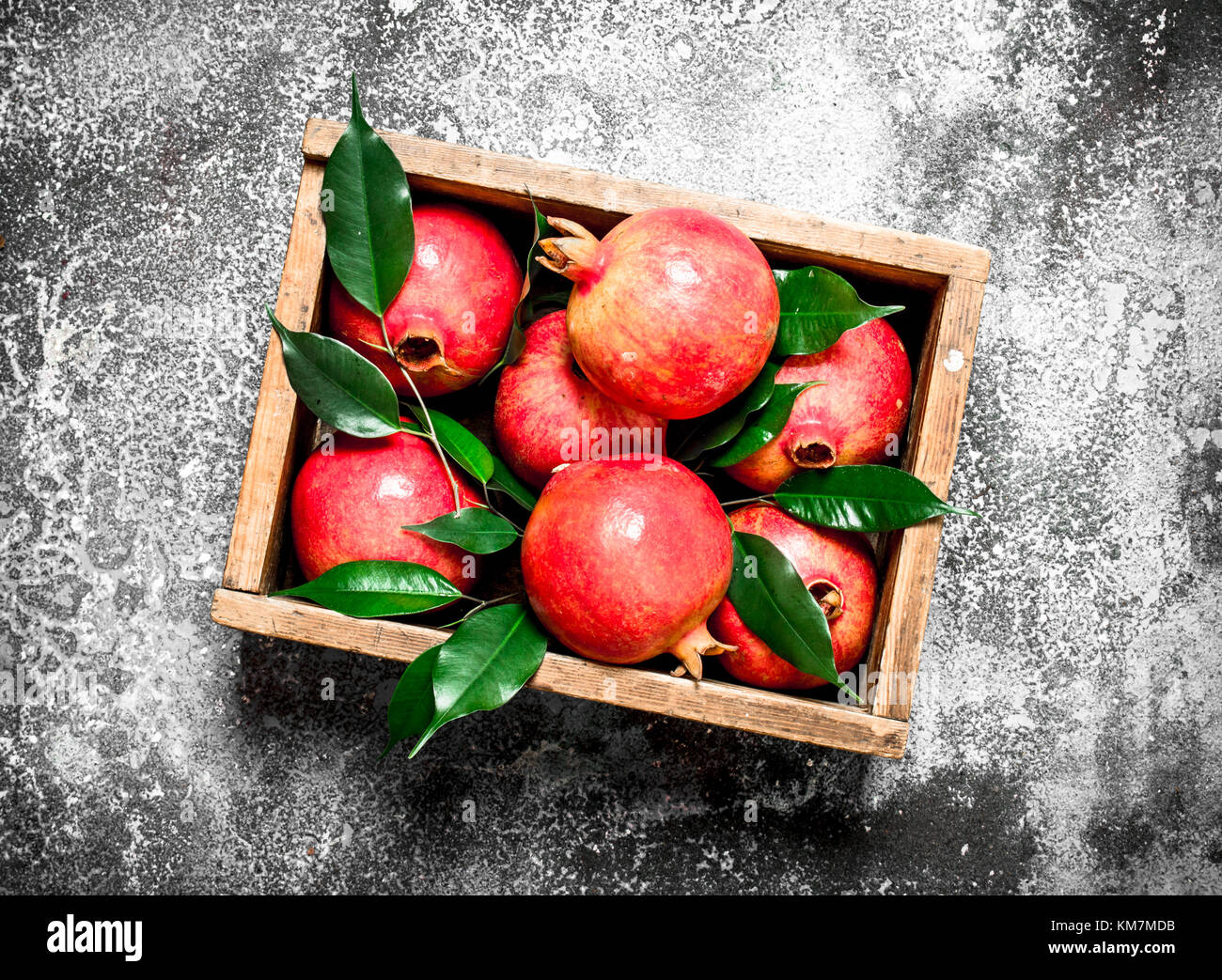 Ripe pomegranates in a box. On rustic background. - Stock Image