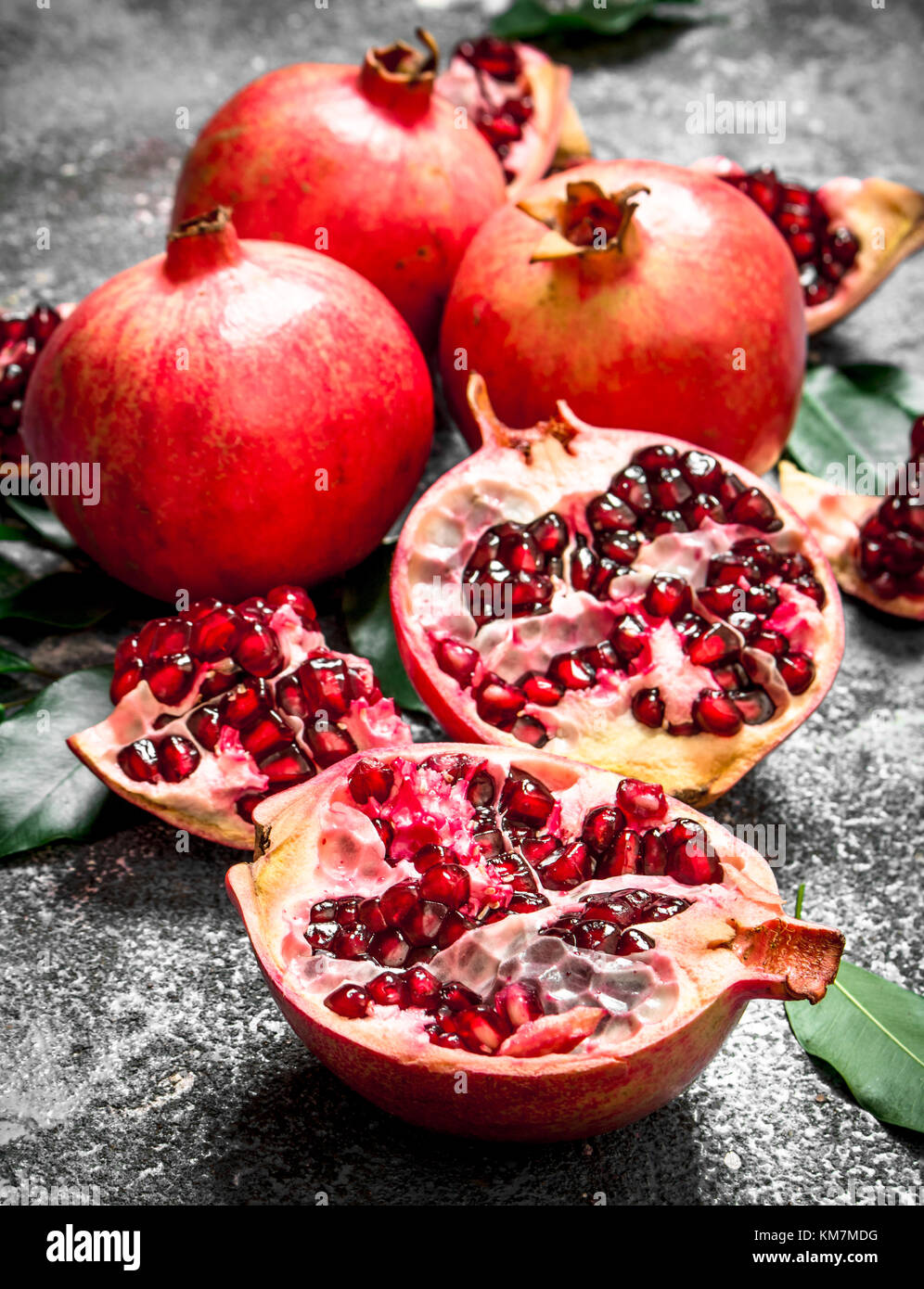 Fresh pomegranates with green leaves. On rustic background. - Stock Image