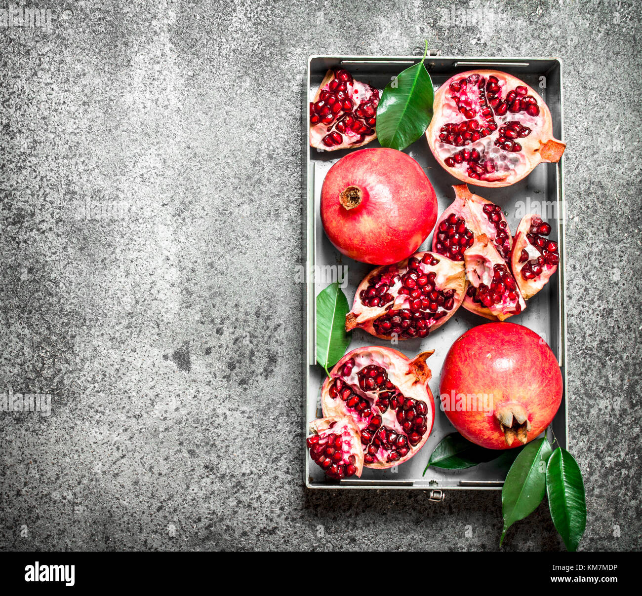 Fresh pomegranates in the old tray. On rustic background. - Stock Image