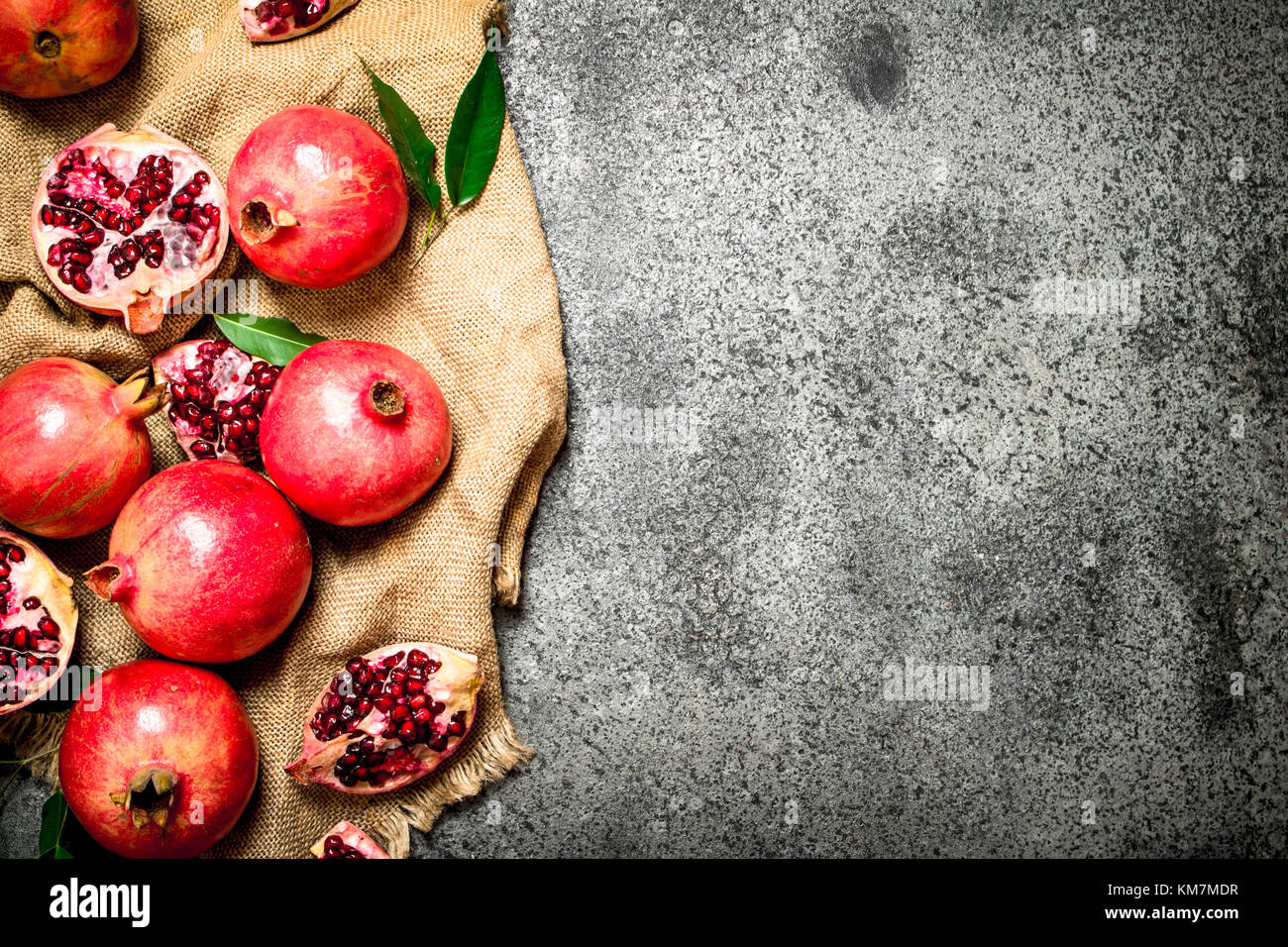 Fresh pomegranates on an old sack. On rustic background. - Stock Image
