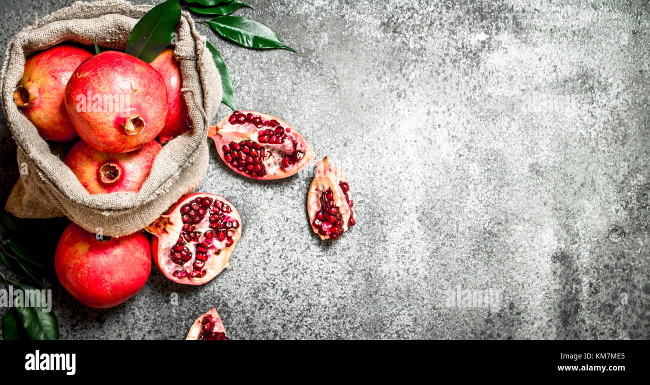Pomegranates in the old bag. On rustic background. - Stock Image