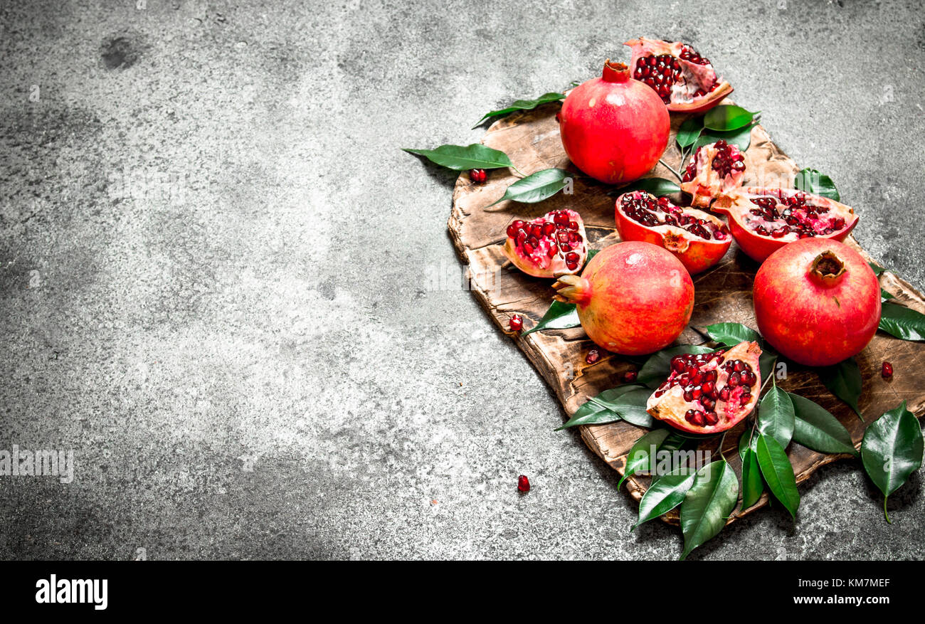 Ripe fresh pomegranates. On the rustic background. - Stock Image