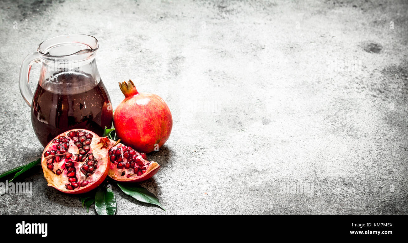 Fresh pomegranate juice in a glass jug. On rustic background. - Stock Image